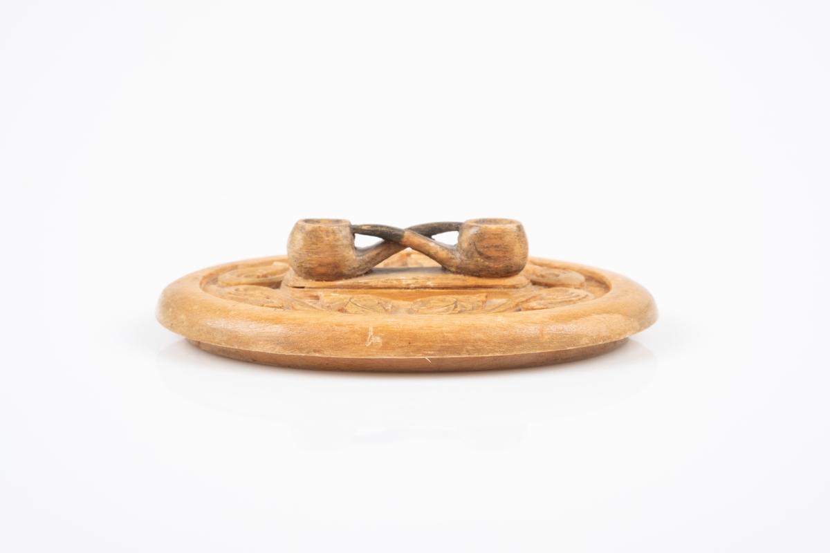 Et ovalformet lokk til tobakksskrin. Lokket har utskjæringer av akantusblader og to tobakksspiper som fungerer som håndtak.