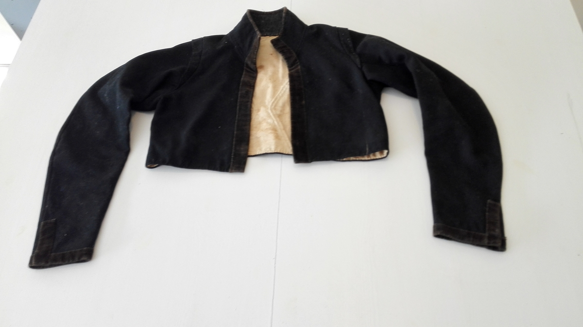 "1 brudetröie.  Brudetröie av sort klæde, kantet med brun flöiel og foret med hvit linlærred. Oputstaaende stukket krave. Har utomliggende kant langs armforbindelsen med skulderen, saakaldt ""barduner"". Hegtes sammen foran med to hegter og maljer. Den oprindelige sölvstas tat bort. Brudetröien har været benyttet i 1823 av Synneva Hermundsd. Fitje f. 1803 (nuværende prost i Aurland Gunnarsons bedstemor).  Kjöpt av Sunneva Gunnarsdatter Thune, Ortnevik."
