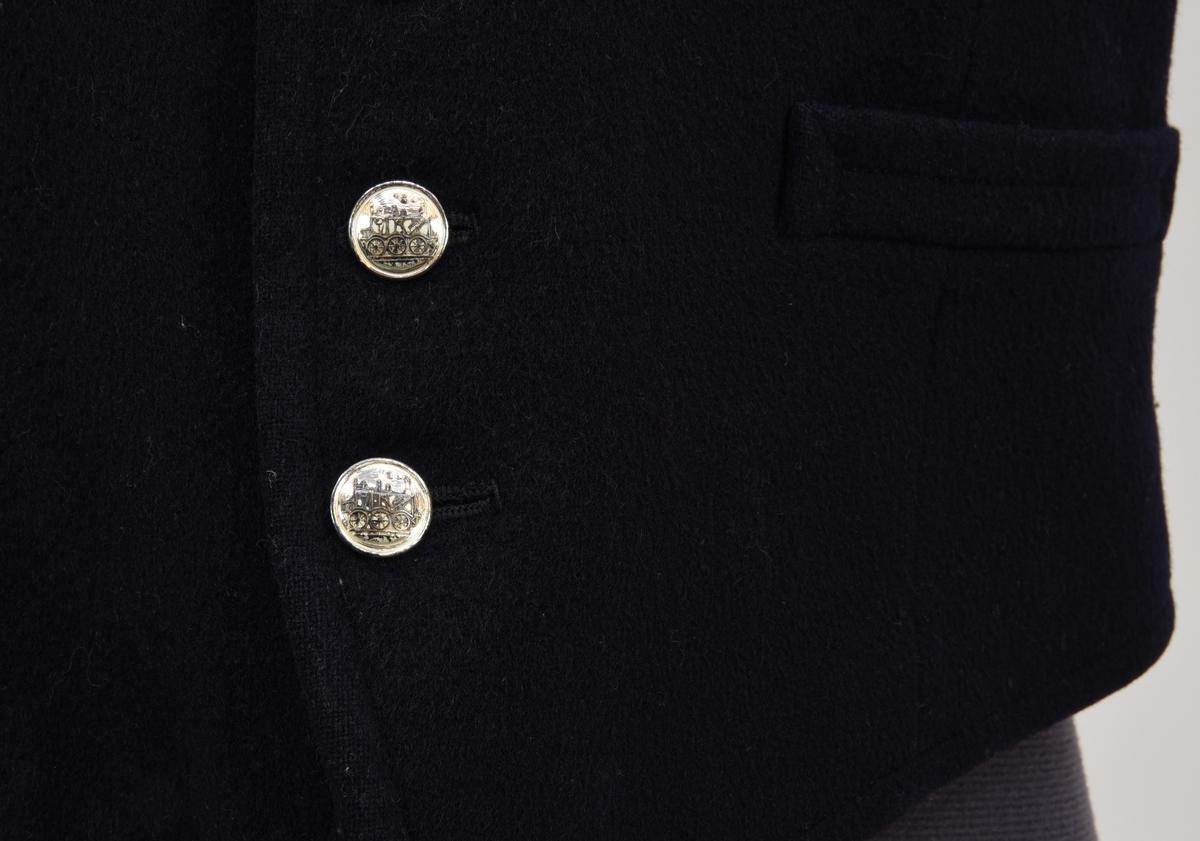 Väst med framsida av mörkblått kläde samt baksida av svart textil, med två stycken sidofickor. Kavajen är fodrat med ett vitt bomullstyg med smala bruna ränder i grupper om tre. Dn knäpps med sju försilvrade metallknappar med lok på framsidan. På västens insida sitter en tillverkarlapp av textil fastsytt. Bokstaven Ö återfinnns skrivet med bläck i nacken.