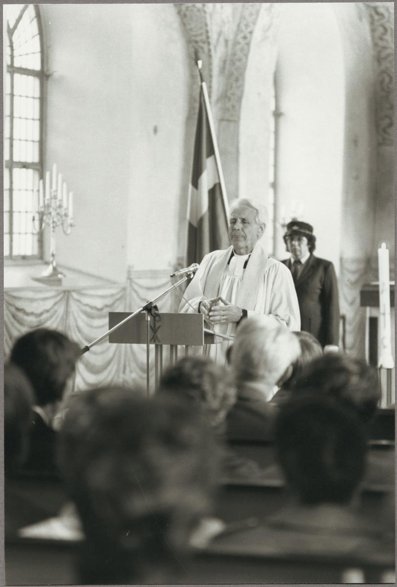 Kyrkoherde Lars Byström talar i Torshälla kyrka på Trafikaktiebolaget Grängesberg - Oxelösunds Järnvägar, TGOJ-dagen den 22 maj 1987. Fanbärare Ingeborg Jakobsson står i bakgrunden.