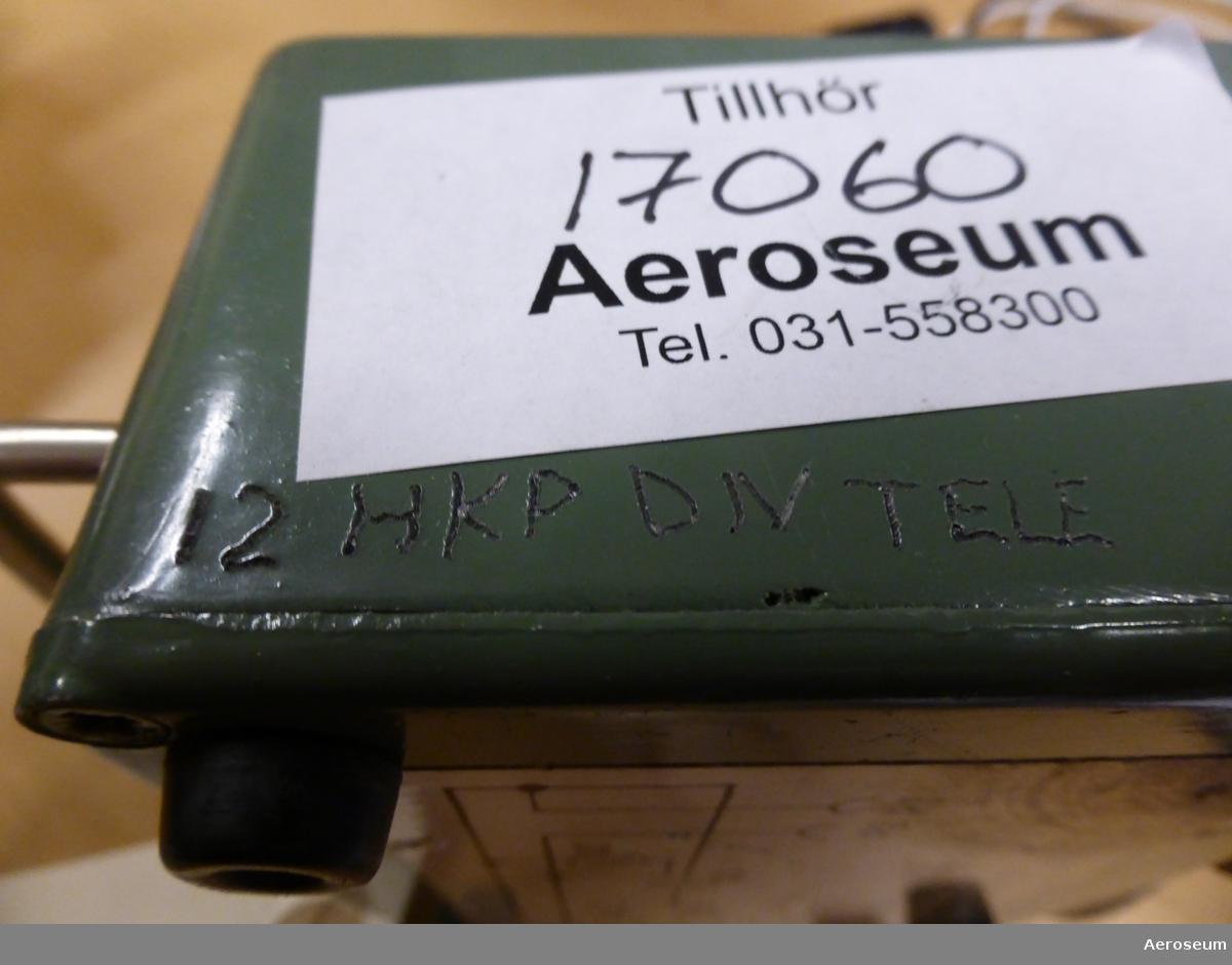 """Ett provningsdon i grågrönmålad metall. Till för tidrelä vinsch på HKP4. På ena sidan står det inristat: """"12 HKP DIV TELE"""". På botten av föremålet finns ett kretsschema ritat på en papperslapp fastklistrat. en grå sladd med ett vitt tygskydd sitter fast i föremålet och i slutet av sladden finns en grå kontakt med skruvbart skyddslock.   Kopplat till föremålets M-nummer (M3742-835610) finns ritningsnummret """"F1230-200859"""" kopplat, som även står med på en metallplatta som är fastskruvat på provningsdonet. Utöver det står ett annat F-nummer på papperslappen med kretsschemat: """"F1230-403726""""."""