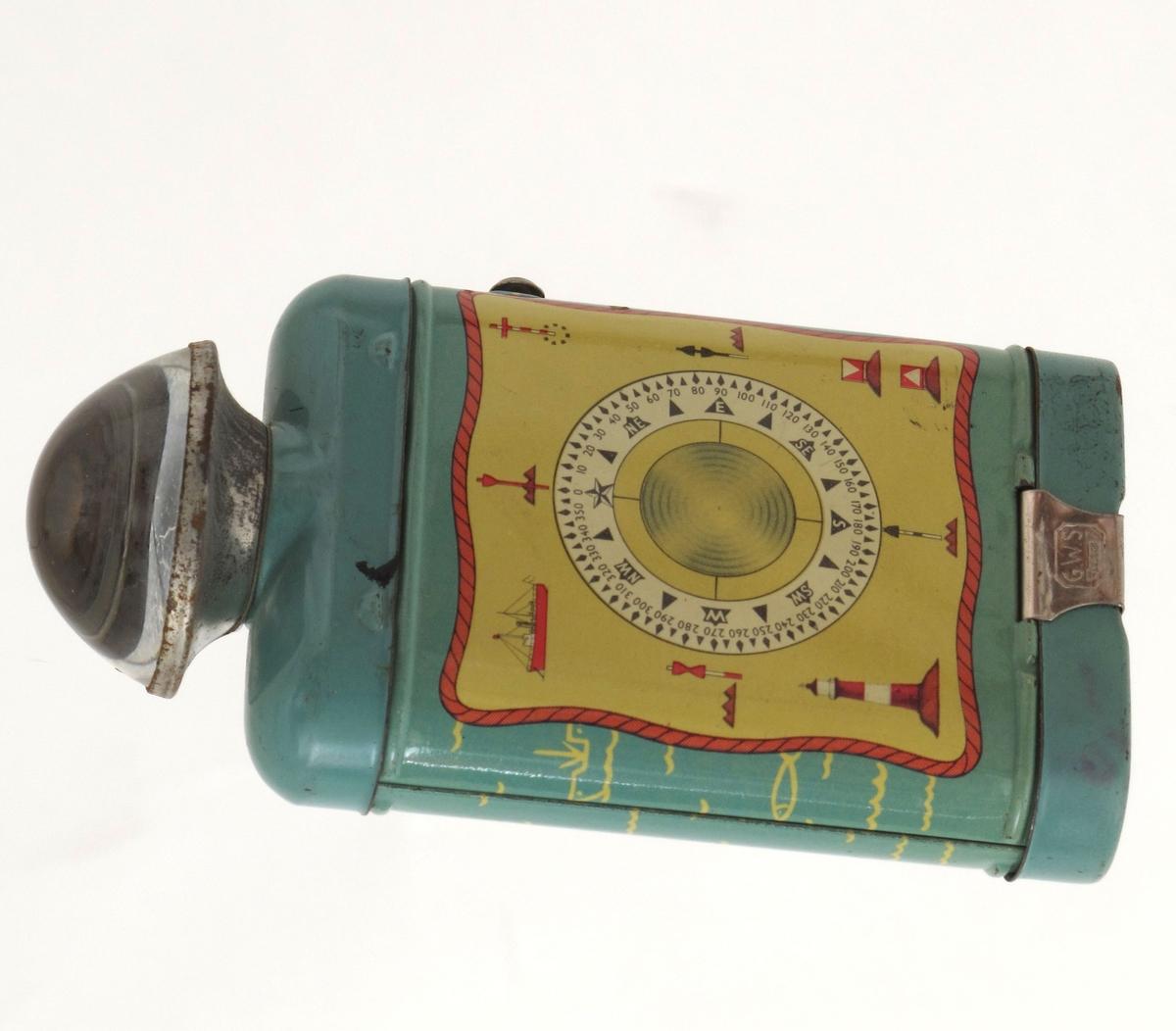 Lommelykt for ett flatt batteri. Glass med linse som sprer lyset.  Lys grønn farge. Dekorert med morsealfabet på ene side, kompassrose, skip, fyrlykt mm på den andre.