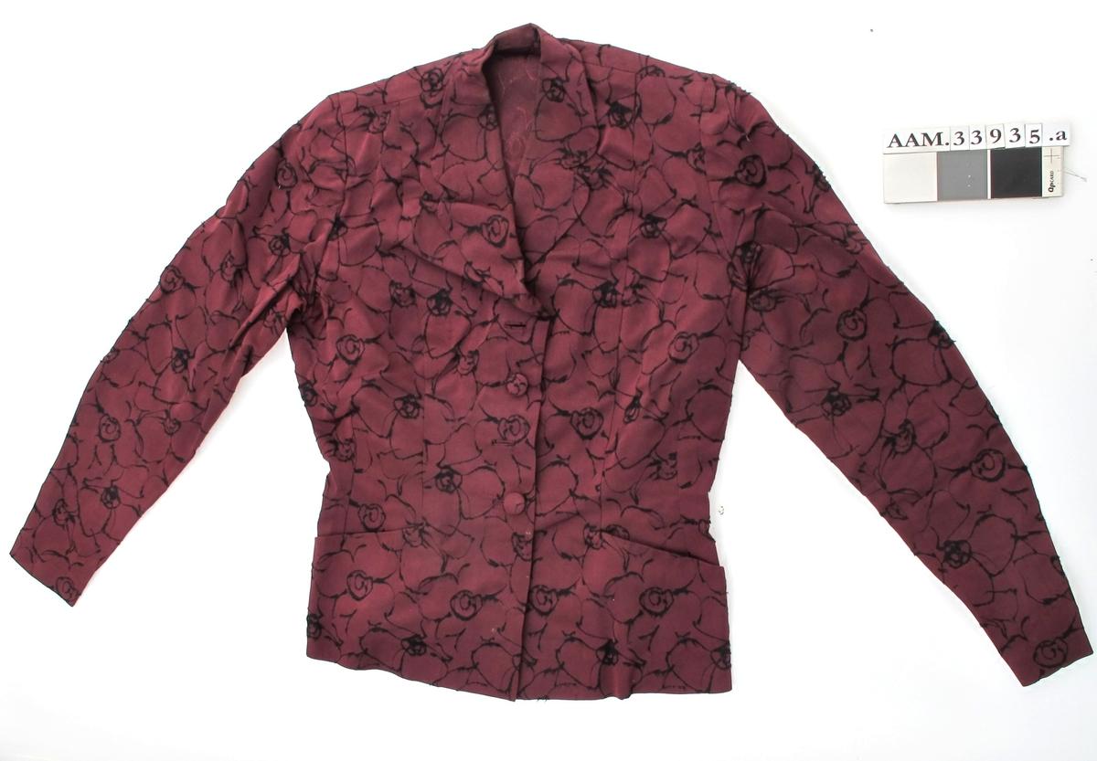 Todelt kjole av stivt fiolett mønstret kunststoff.