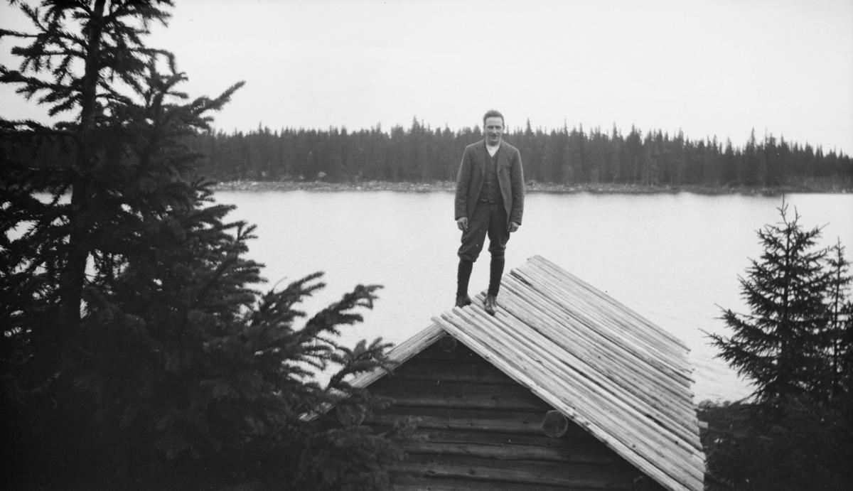 Mann stående på taket til ei fiskerbu eller et båtnaust