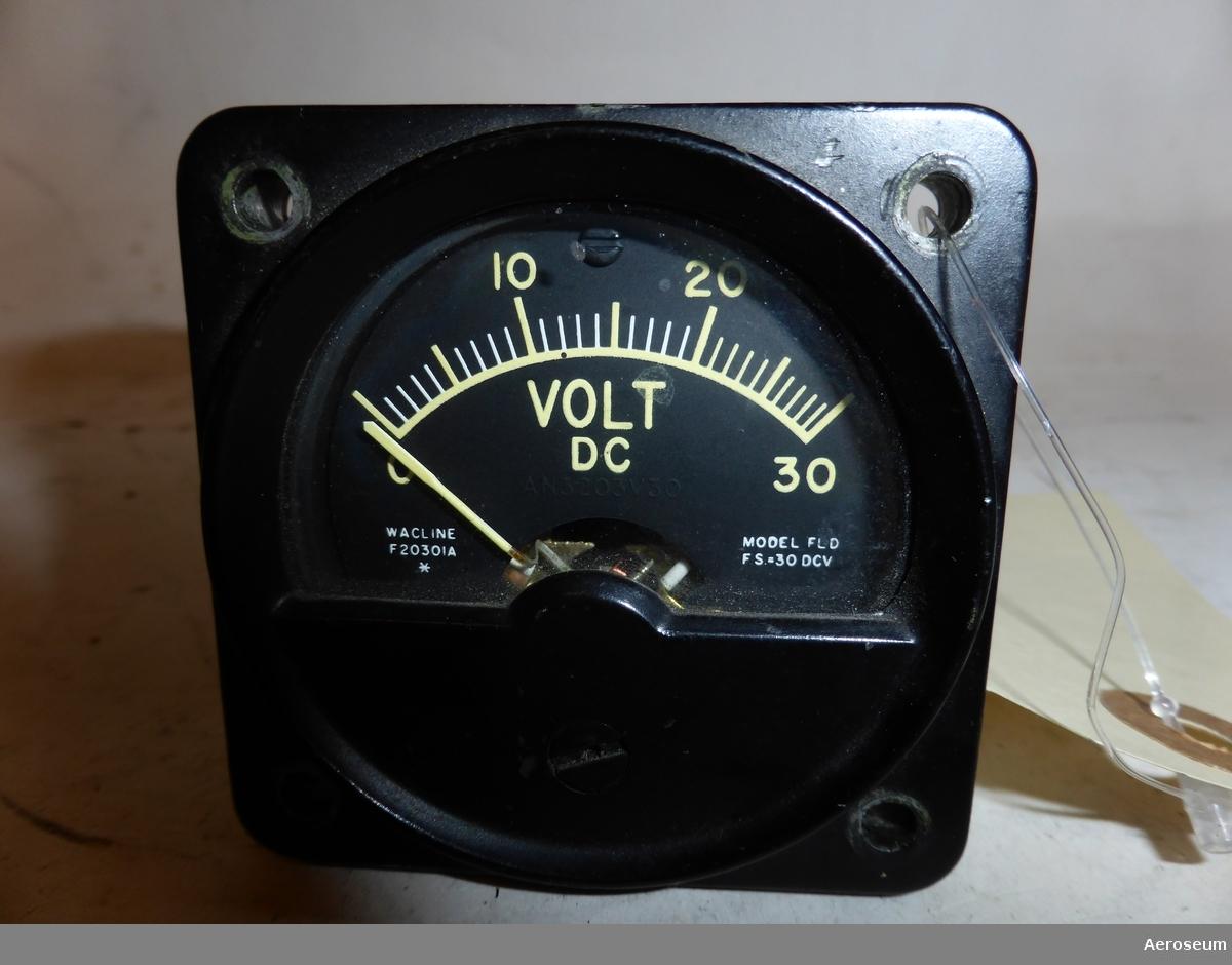 "En voltmeter i metall. Tillverkad av Wacline. I displayen står det: ""VOLT DC AN3203V30 WACLINE F2030IA * MODEL FLD FS=30 DCV"". I botten står det: ""7001 SEALED DO NOT OPEN""."