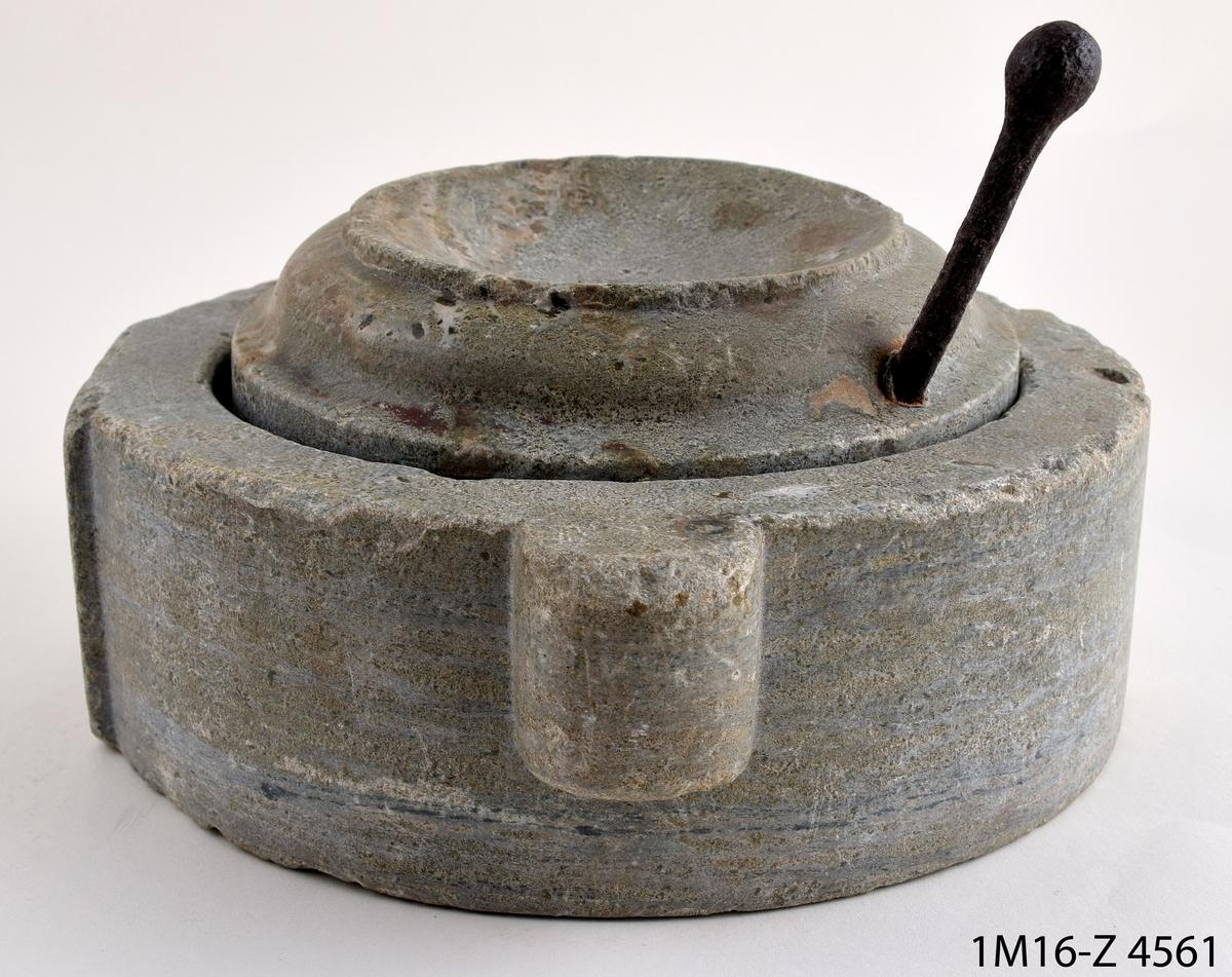 Handkvarn, av kalksten och metall, rund. Handkvarnen består av en liggare och en löpare. Huggna räfflor på handkvarnens malytor. Metallpigg i mitten på liggaren, på utsidan två handtag samt ett tapphål. Löparen är profilerad med en vridpinne av järn. I mitten av löparen ett runt hål.