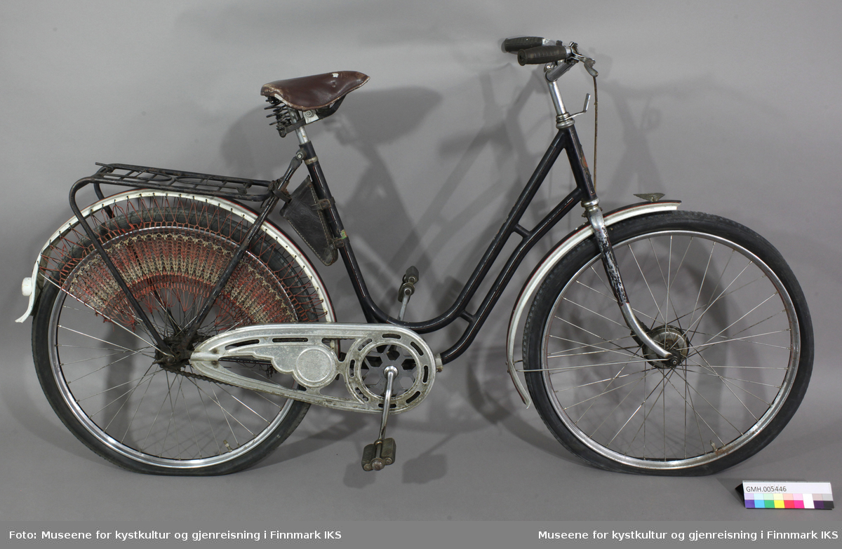 Sykkelen er sort og har bagasjebrett og skjermer. Skjermen på forhjulet har en vinge med spissen mot fartsretningen (stiftet fast.) På bakskjermen er det det stiftet en rund utstikker med rød refleks. Bakhjulet er kledd med en netting for å hindre at klær setter seg fast i bakhjulet. Styret har sorte plasthåndtak og på høyre siden er det ei håndbrems (antatt). På venstre side er det ei bjelle/ringeklokke Sykkelen har en kjedebeskytter. På beskyttelsen/lokket er det inngravert navnet til eier: Bodil Knudsen, H-fest. Setet er brunt og i lær. På ramma under setet er det festet ei lita sadelveske/taske i lær (som smalner mot bunnen) med lokk. I sadelveska er det en avlang, gul-oransje boks med lappesaker. Boksen har følgende påskrift: DUNLOP - LONG CYCLE - REPAIR OUTFIT.