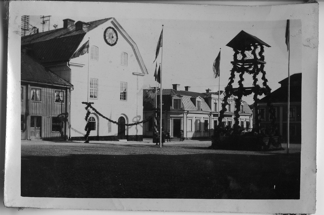 Rådhuset med klockstapel på Stora torget. Kvarteret Kungsgården ses i bakgrunden. Flaggorna är hissade. Avfotograferat fotografi