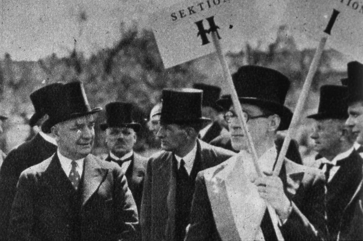Riksdagens 500-årssjubileum firas i Arboga. Här ses delar av den svenska regeringen; statsminister Per-Albin Hansson, till vänster och finansminister Ernst Wigfors till höger. Alla män bär stormhatt.