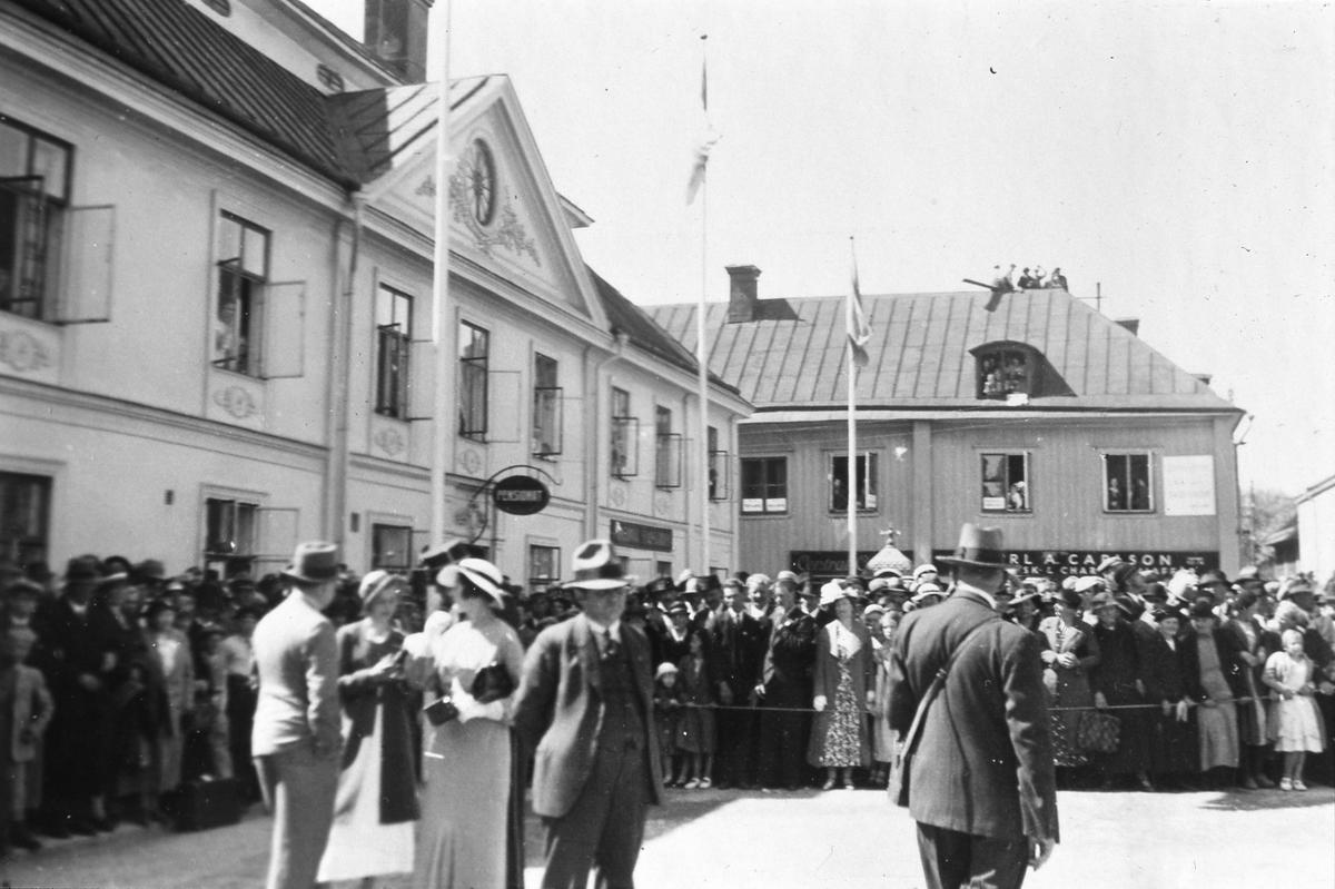 Människor är samlade på Stora torget i väntan på kung Gustaf V´s ankomst. Han, och en stor del av kungahuset, ska närvara vid Riksdagens 500-årsjubileum som firas i Arboga. Människor står bakom avspärrningar. Fönstren är öppna på pensionatet i Stadsgården så människor kan titta ut. I fastigheten på Västerlånggatan 1 sitter det till och med folk på taket. Flaggorna är hissade. (Arbogautställningen pågår samtidigt).