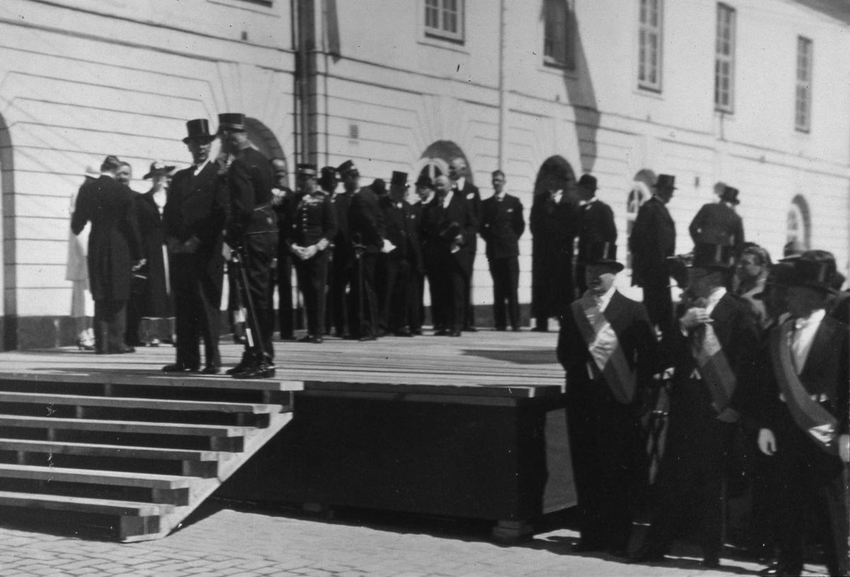 En scen är uppbyggd intill Rådhuset. Uppklädda män och kvinnor väntar på Kungens ankomst. Några bär uniform, andra har stormhatt och ordnar. Gustav V, och många medlemmar av kungafamiljen, ska delta i Riksdagens 500-årsjubileum som ska firas i Arboga. Kungen ska komma, med bil, från Stockholm. Arbogautställningen pågår samtidigt. Kungen ska hinna besöka den också.