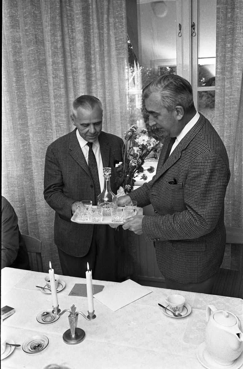 Alf Hedlund, maskinmästare, går i pension från Centrala Verkstaden Arboga. Anders Högfeldt uppvaktar med blommor och present.  Män i kostym. Vit duk med kaffekoppar. Blombukett och karaff med glas i present.