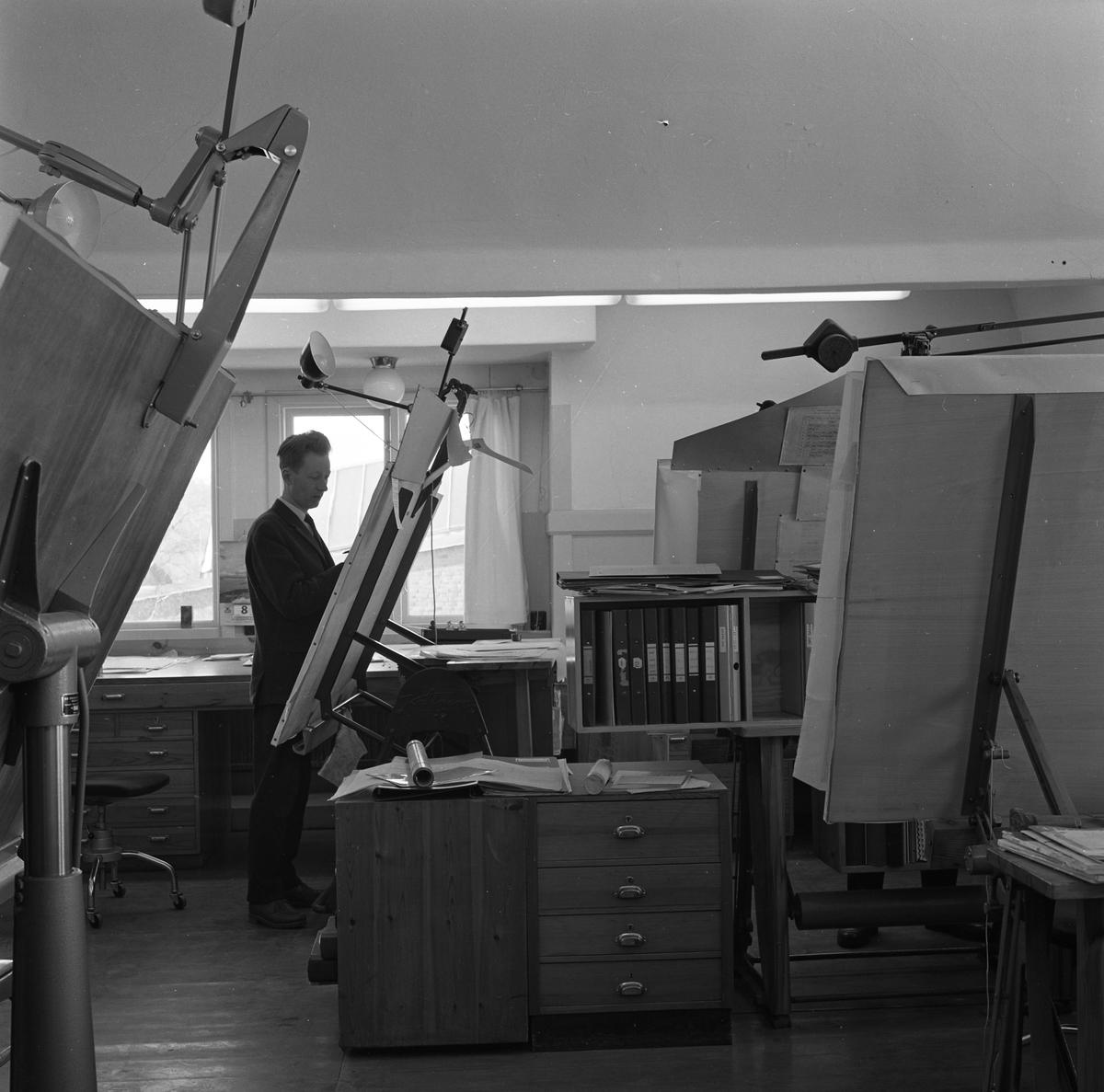 """Curt Ericson på ritkontoret på """"Meken"""", Arboga Mekaniska Verkstad. Interiörbild från kontoret. Kostymklädd man vid ritbord, bokhylla med pärmar inom räckhåll."""