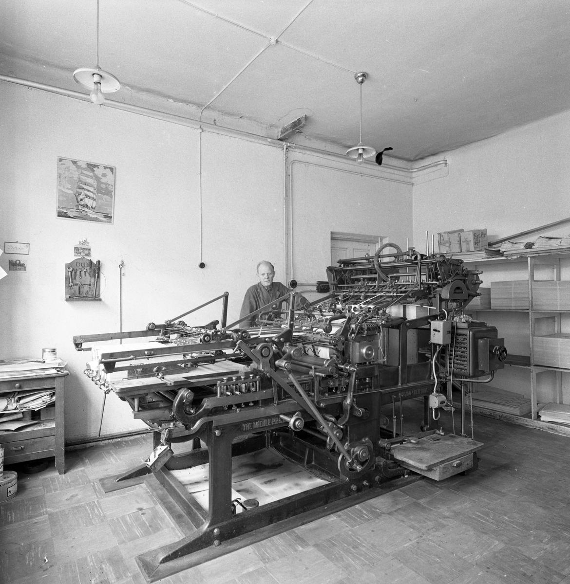 Arboga Boktryckeri, interiörbild från 1950-talet. En man, iklädd arbetsrock står bakom en stor maskin. En byrå till vänster och hyllor till höger.
