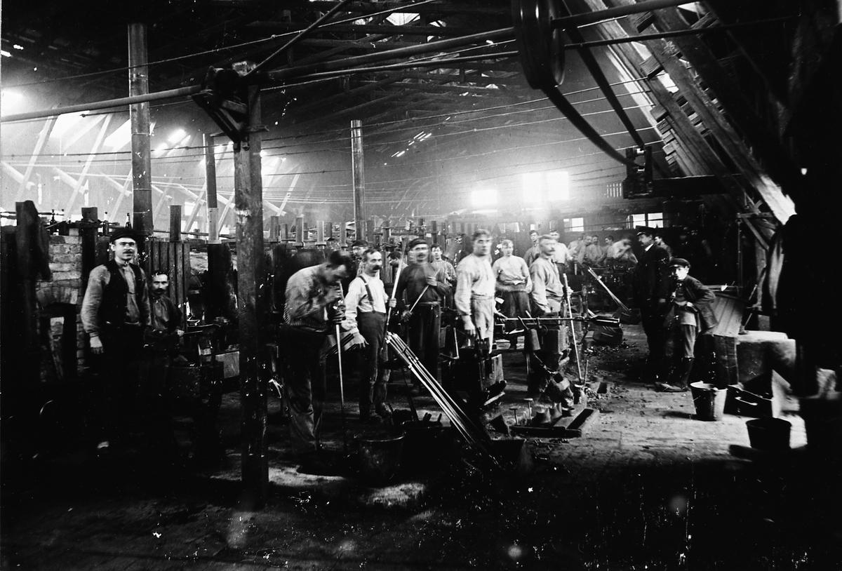 """Arboga Glasbruk, interiör. Avfotograferat fotografi. Ursprunglig fotograf okänd. Män och unga pojkar arbetar i glasbruket. I mitten av bilden syns en glasblåsare i aktion.  Uppgifterna om vilket år glasbruket etablerades varierar; 1867, 1870 och 1874 är exempel.  Bolagsordningen, för Arboga Glasbruks AB, stadfästes 1875. Bruket anlades nära hamnen och järnvägen. Buteljer fraktades till Stockholm med lastångaren """"Trögelin"""". På glasbruket tillverkades ca 400 olika sorters flaskor, olika storlekar inräknade. Glasbruket lades ner 1928.  Läs om Arboga Glasbruk i Hembygdsföreningen Arboga Minnes årsböcker 1982 och 2011."""