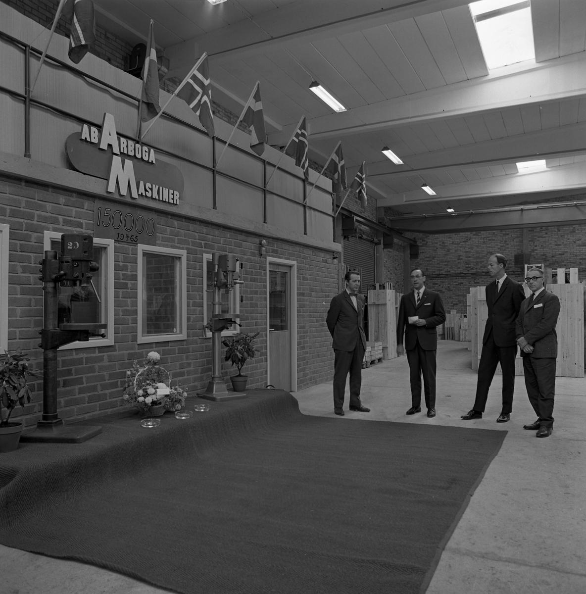 Arboga Maskiner firar maskin nummer 150 000. Fyra kostymklädda herrar väntar intill ett podium med två pelarborrmaskiner och en blomsteruppsättning. Flaggor är uppsatta på väggen.  AB Arboga Maskiner startade 1934 och tillverkar borr- och slipmaskiner.  En bild, från detta tillfälle, finns med i Reinhold Carlssons bok Arboga objektivt sett.