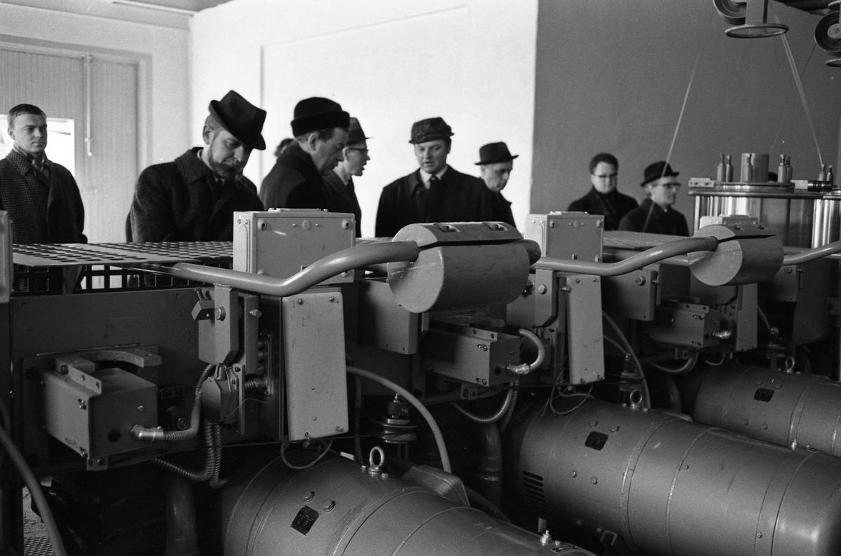 Arboga Mekaniska Verkstad, interiör. Kunder besöker Meken för att titta på tråddragmaskiner. Herrar i ytterkläder studerar maskiner.  25 september 1856 fick AB Arboga Mekaniska Verkstad rättigheter att anlägga järngjuteri och mekanisk verkstad. Verksamheten startade 1858. Meken var först i landet med att installera en elektrisk motor för drift av verktygsmaskiner vid en taktransmission (1887).  Gjuteriet lades ner 1967. Den mekaniska verkstaden lades ner på 1980-talet. Läs om Meken i Hembygdsföreningen Arboga Minnes årsbok från 1982.