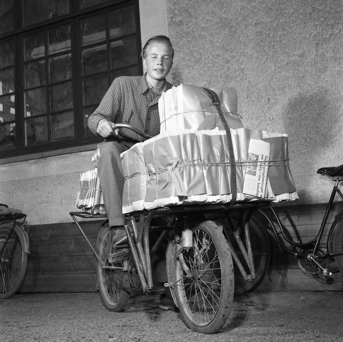 Arboga Tidning, personal. En ung man sitter på en cykel fullastad med tidningar som ska levereras. Tidningsbuntarna hålls på plats av snören och en lång läderrem.
