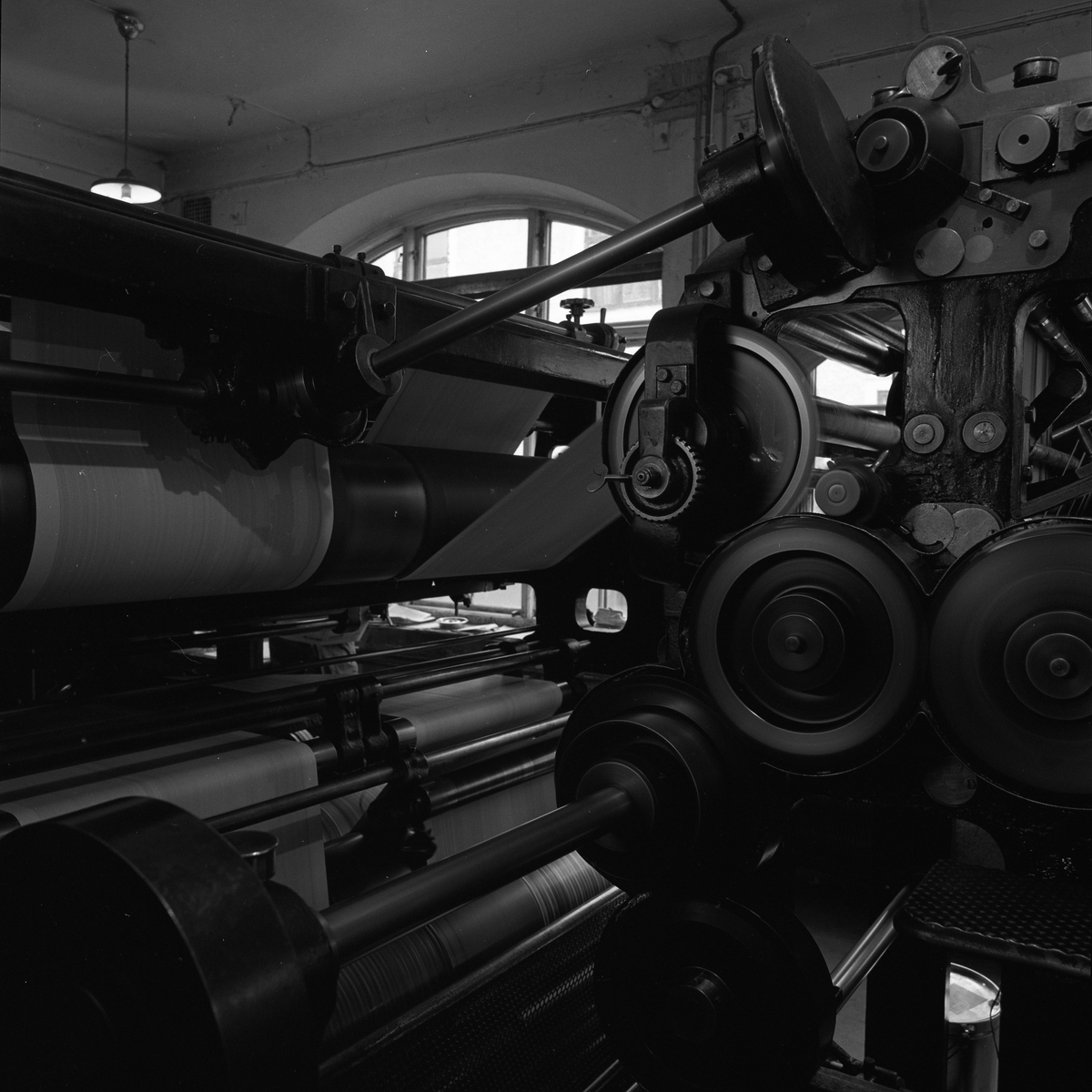 Arboga Tidning, interiör. Den stora tryckpressen matar fram färdiga tidningssidor på pappersrulle.
