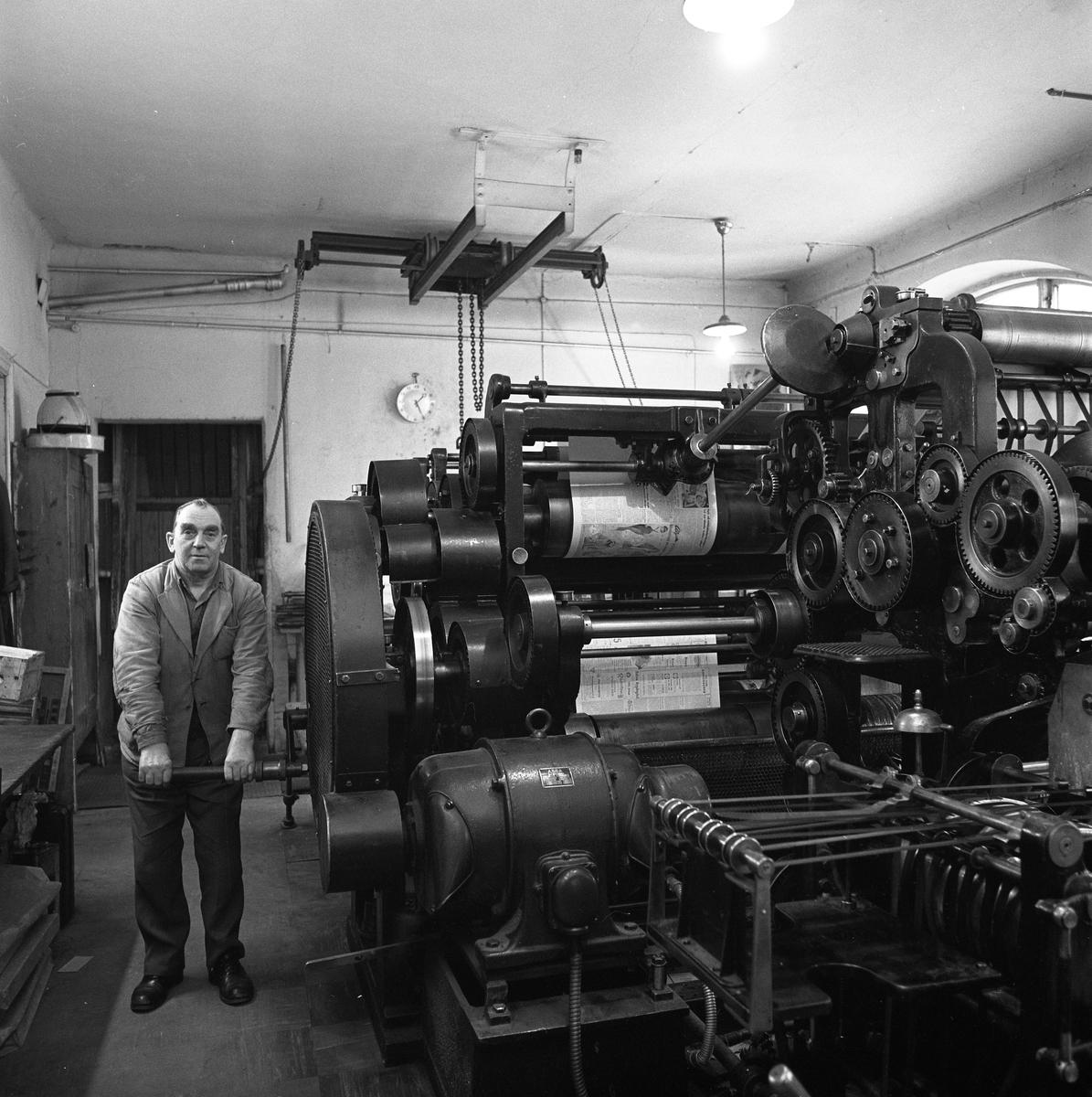 Arboga Tidning, personal och interiör. En man håller i en vev till en stor tryckpress. De färdigtryckta tidningssidorna syns på valsarna.