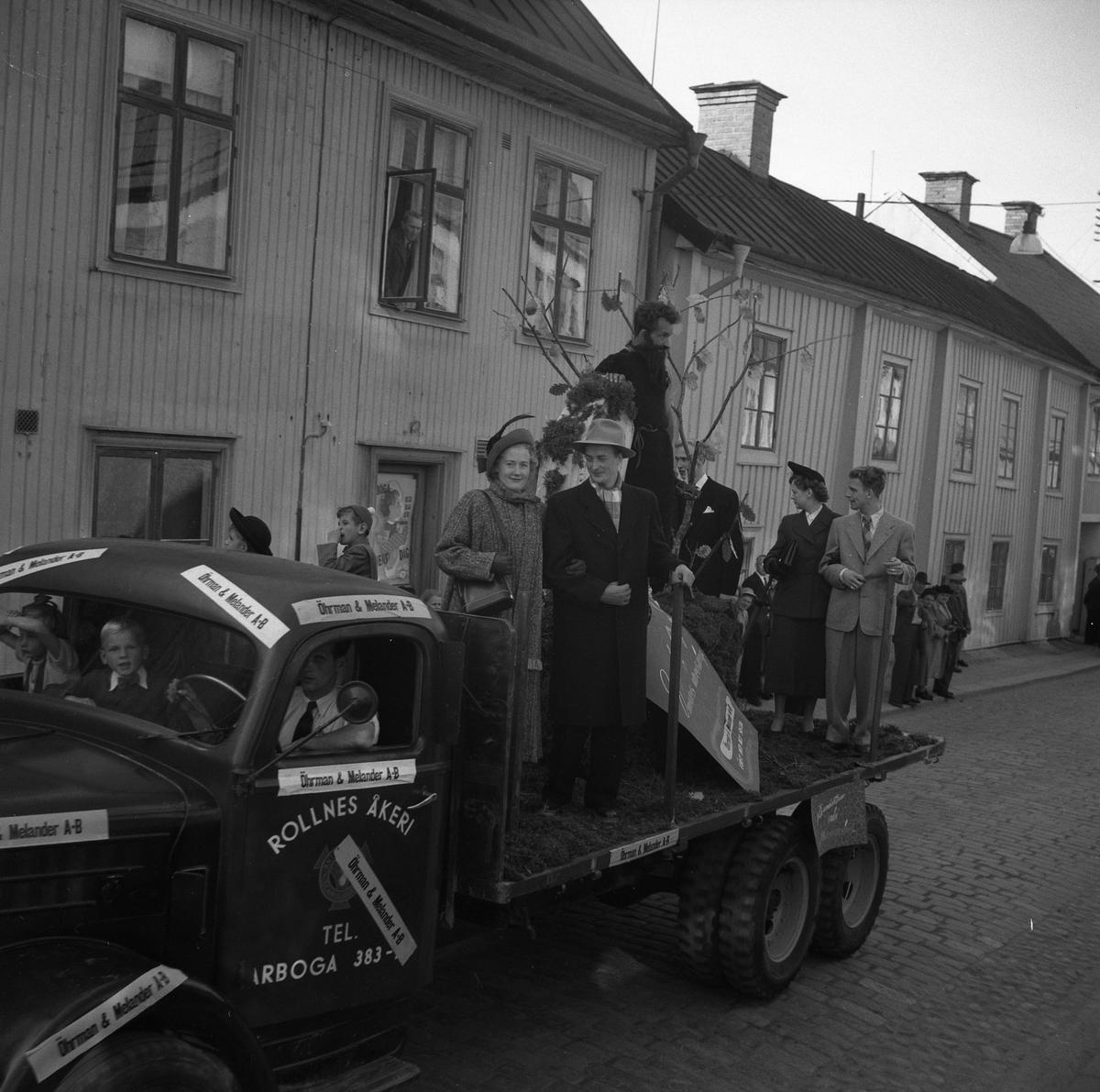 """Rollnes Åkeri deltar i Barnens Dagsfirandet. En man och två barn sitter i förarhytten. På lastbilen är det klistrat lappar med texten """"Öhrman och Melander"""". På lastbildsflaket står några vuxna i ytterkläder, förmodligen från firman Öhrman och Melander."""