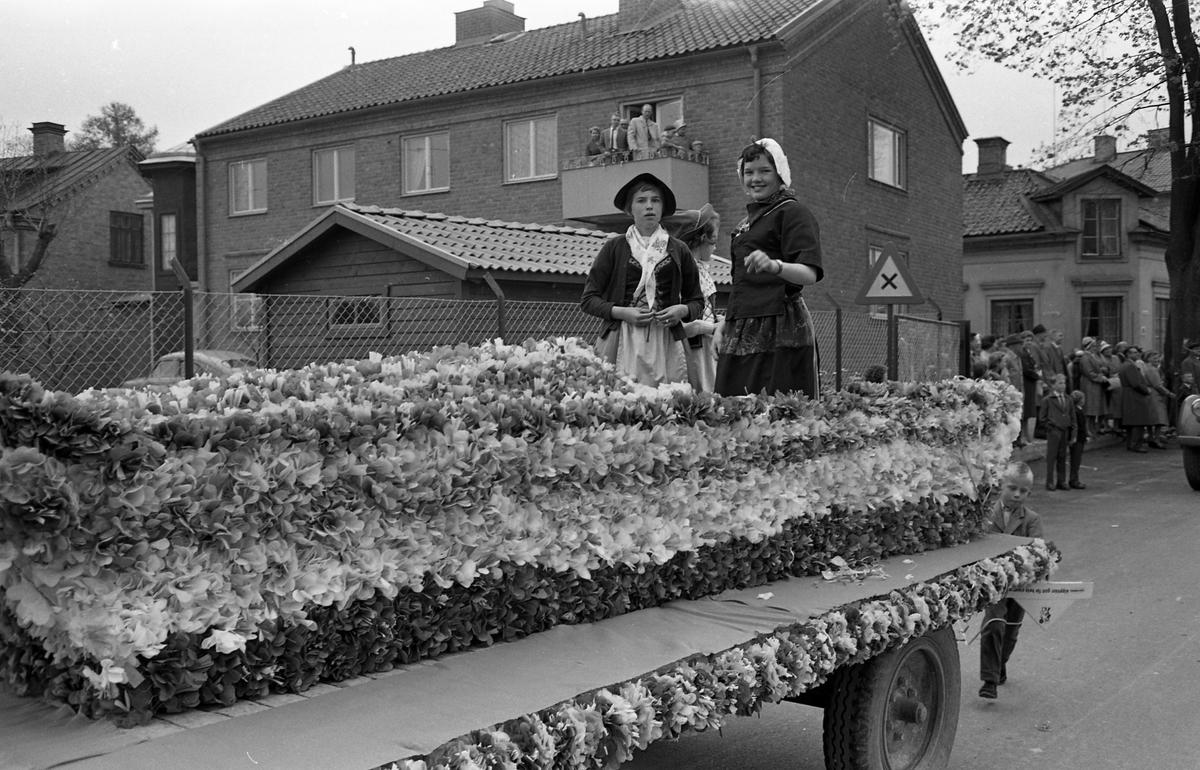 Barnens Dag firas med en kortege genom staden. Här är en blomsterprydd vagn med tre flickor på. Publiken står efter vägen och ser på.