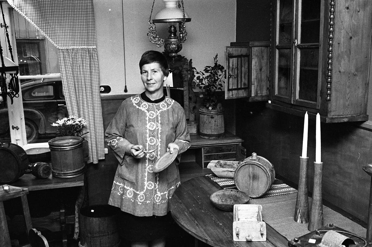 Bellas Antikbod ligger i ett blått hus på Storgatan. Kvinnan är identifierad som Blenda Asplund från Nerikes Kil. Kvinna omgiven av gamla föremål; fotogenlampa, ljusstakar, ett väggskåp, en pigtittare och små trätunnor. Genom fönstret skymtar en PV.