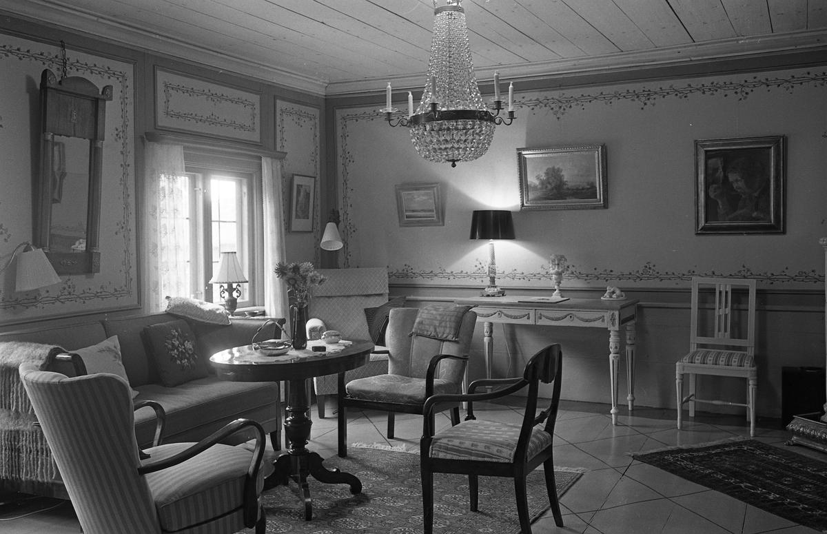 Bostadsinteriör från Crugska gården. Möblemanget består av soffa, pelarbord, karmstolar, skrivbord, och golvlampa. På väggarna hänger tavlor och en stor spegel. En kristallkrona hänger i taket.
