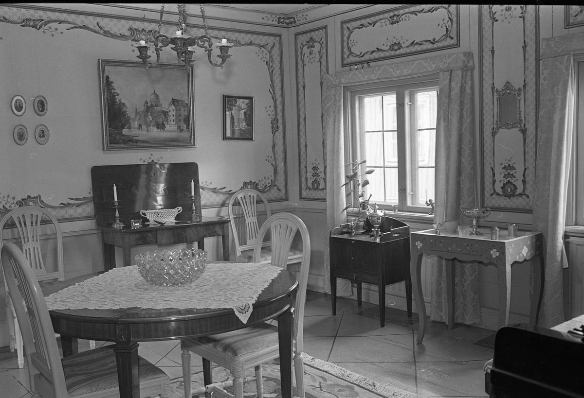 Bostadsinteriör, Crugska gården. Dekorerade väggar. Ett flertal olika möbler bland annat ett bord och fyra stolar. Till höger anas ett piano. En krukväxt på ett bord vid fönstret. Tavlor på väggarna. En ljuskrona i taket.
