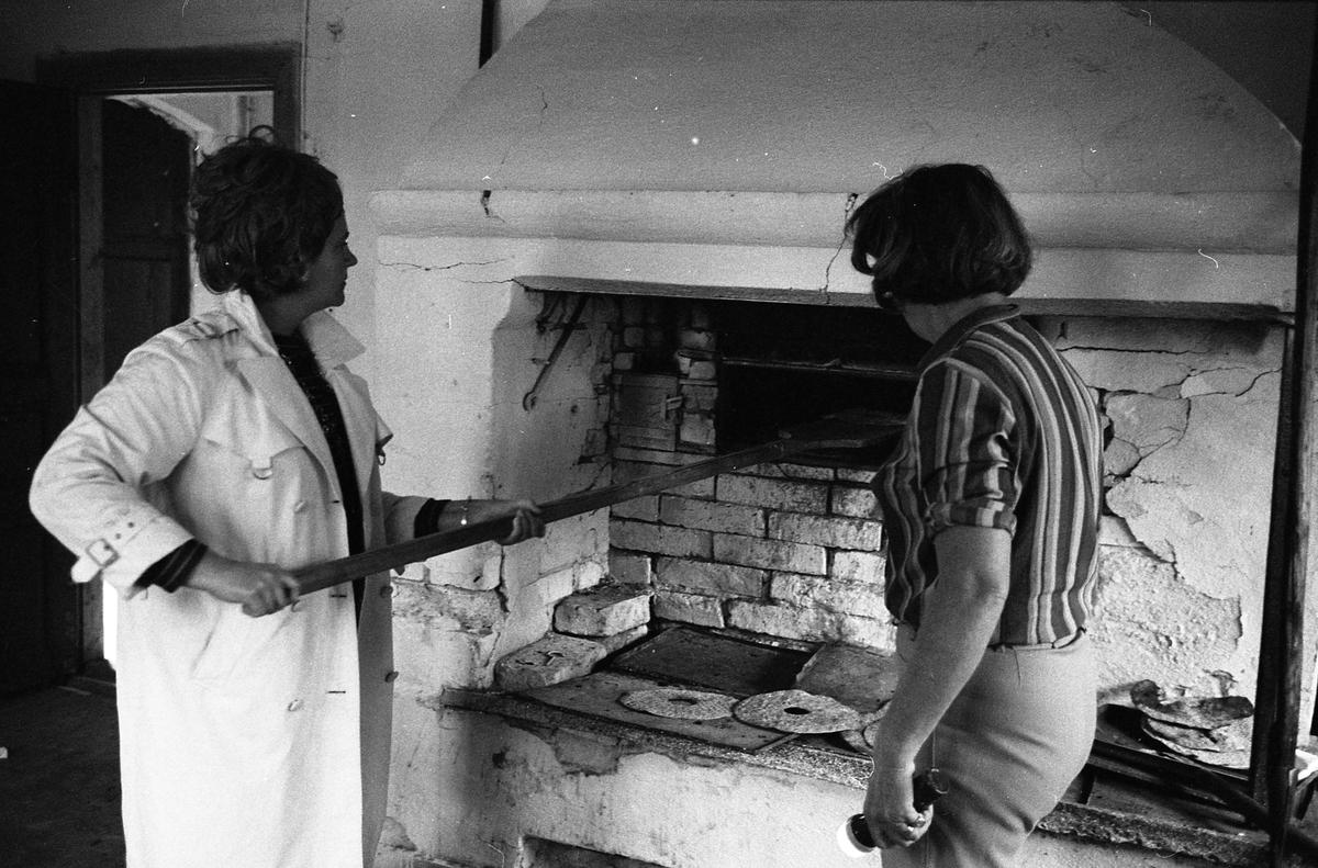 Brödbakning vid Jäders bruk. Två kvinnor i en bakstuga/bagarbod. En kvinna håller i en brödspade som hon sticker ini ugnen. De bakar knäckebröd.