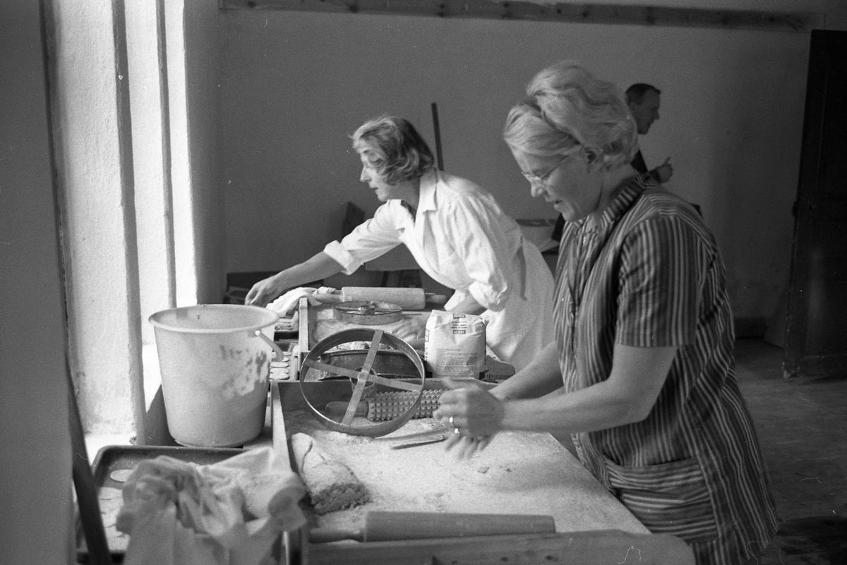 Brödbakning på Jäders bruk. Två kvinnor bakar. På bordet finns mjölpåse och brödkavlar. En man skymtar i bakgrunden.