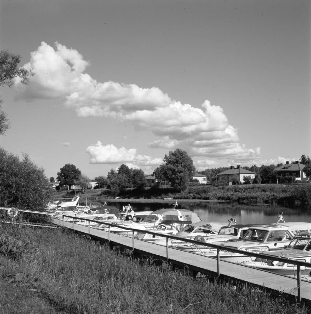 Båtklubbens brygga nedanför Bergmanparken. Småbåtar ligger sida vid sida i Arbogaån. På andra sidan ån ses husen på Södra Ågatan.