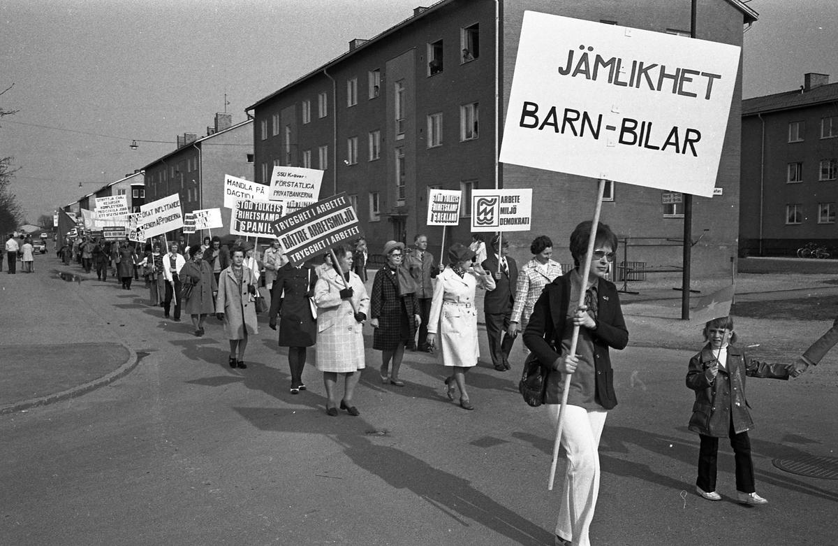 """Demonstration på första maj. Människor demonstrerar och bär plakat.  Plakatet med texten """"Arbete Miljö Demokrati"""" bärs av Gustav Danielsson. Hans hustru Signe tågar vid hans sida, iklädd hatt och rutig kappa."""
