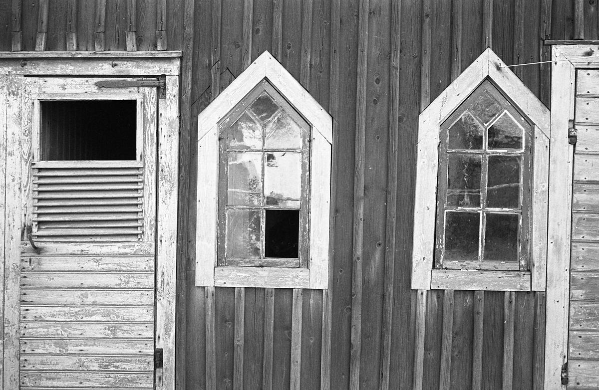 Exteriör. Del av vägg på äldre bebyggelse. Möjligen en trasig dörr till utedasset, två spröjsade fönster (en ruta saknas) samt en förrådsdörr. Fotografens anteckning: Dokumentation av fastigheter i kvarteren söder och norr om ån. Bilder och beskrivning finns på Arboga Museum.