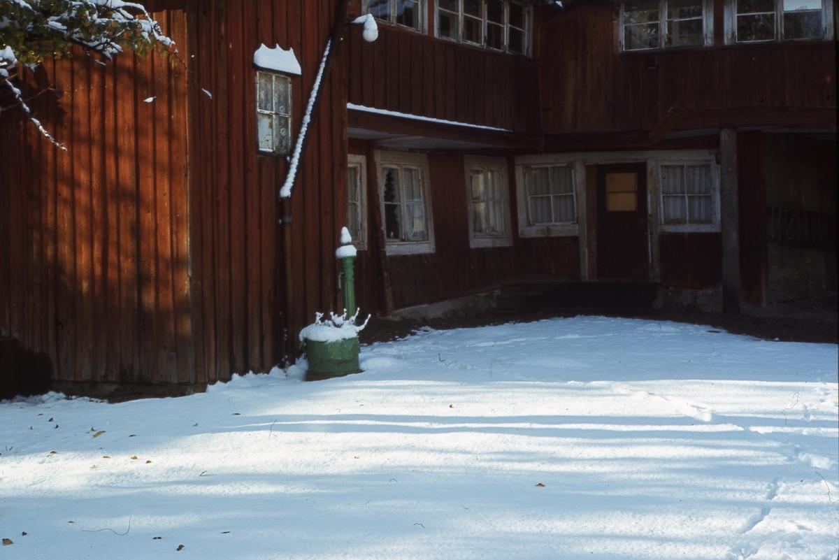 Gammal bebyggelse, trähus i vinkel. Pumpen sticker upp ur snön.