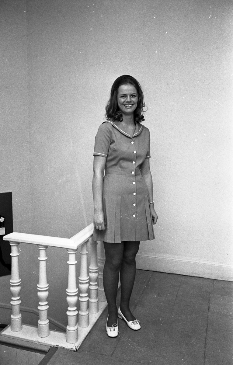 Öhrman & Melander ska ha modevisning. Kerstin Löfgren är en av mannekängerna. Här visar hon en helknäppt klänning med lagda veck i kjolen. Hon står utanför firmans kontor.
