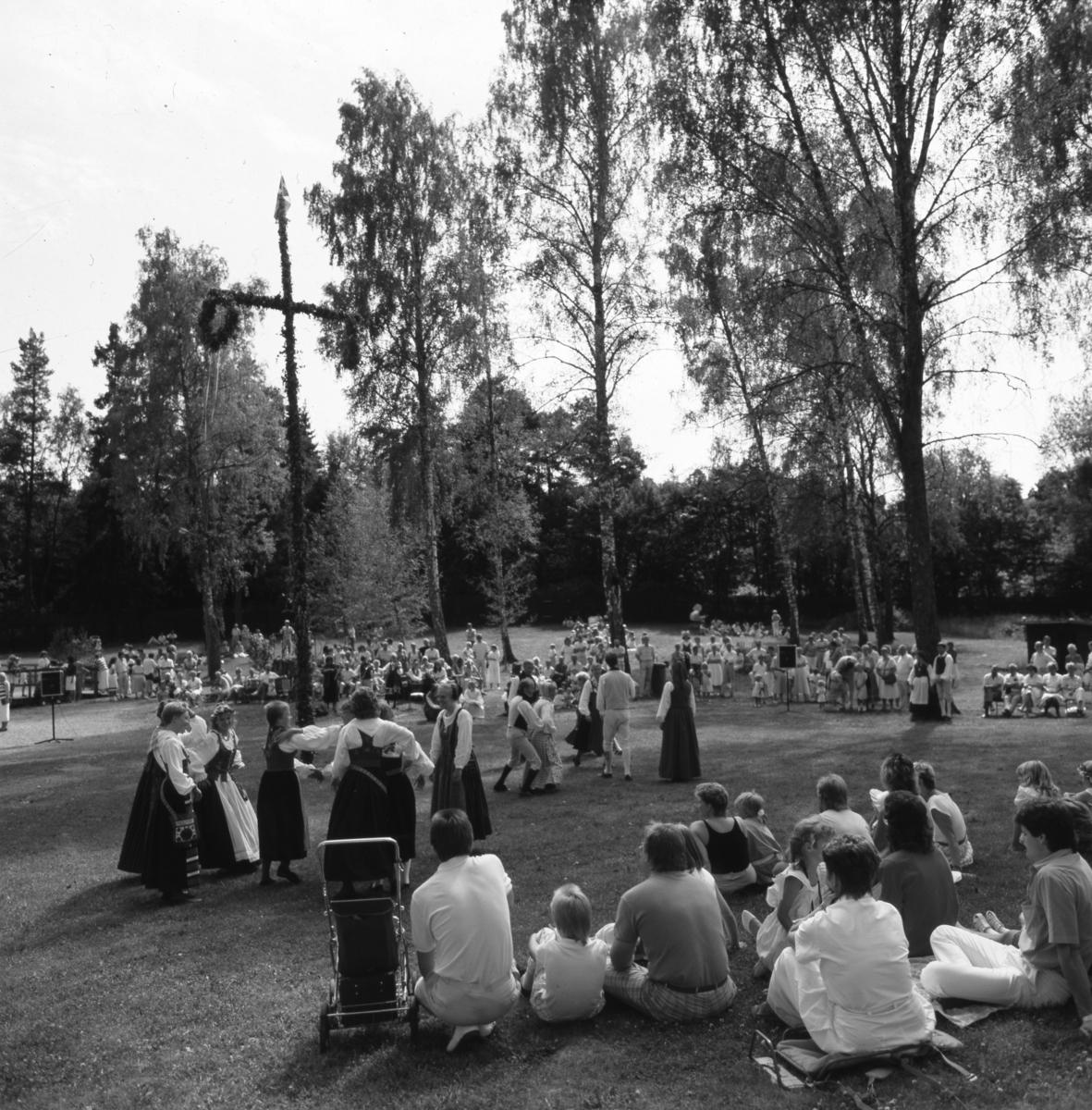 Midsommarfirande i Folkets park. Folkdanslaget har uppvisning intill midsommarstången medan publiken sitter i gräset och ser på. Flaggorna är hissade och solen skiner.