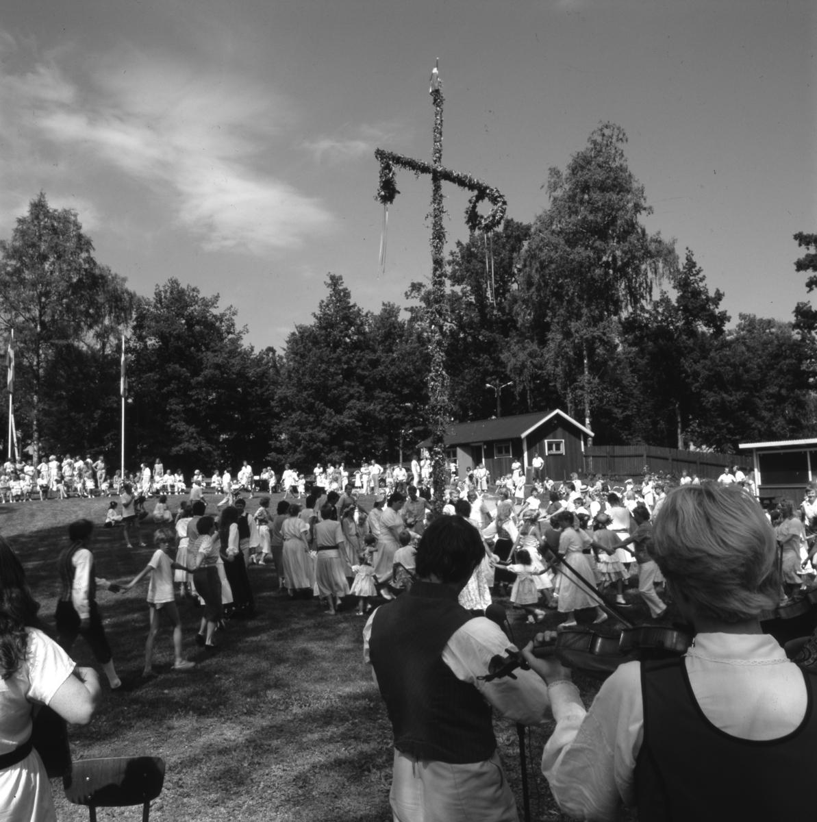 Midsommarfirande i Arboga Folkets park. Midsommarstången är rest och dansen pågår för fullt; mest är det kvinnor och barn som deltar. Närmast kameran står spelmännen. Bakom dansarna ses glasskiosken. Flaggorna är hissade och det är vackert väder.