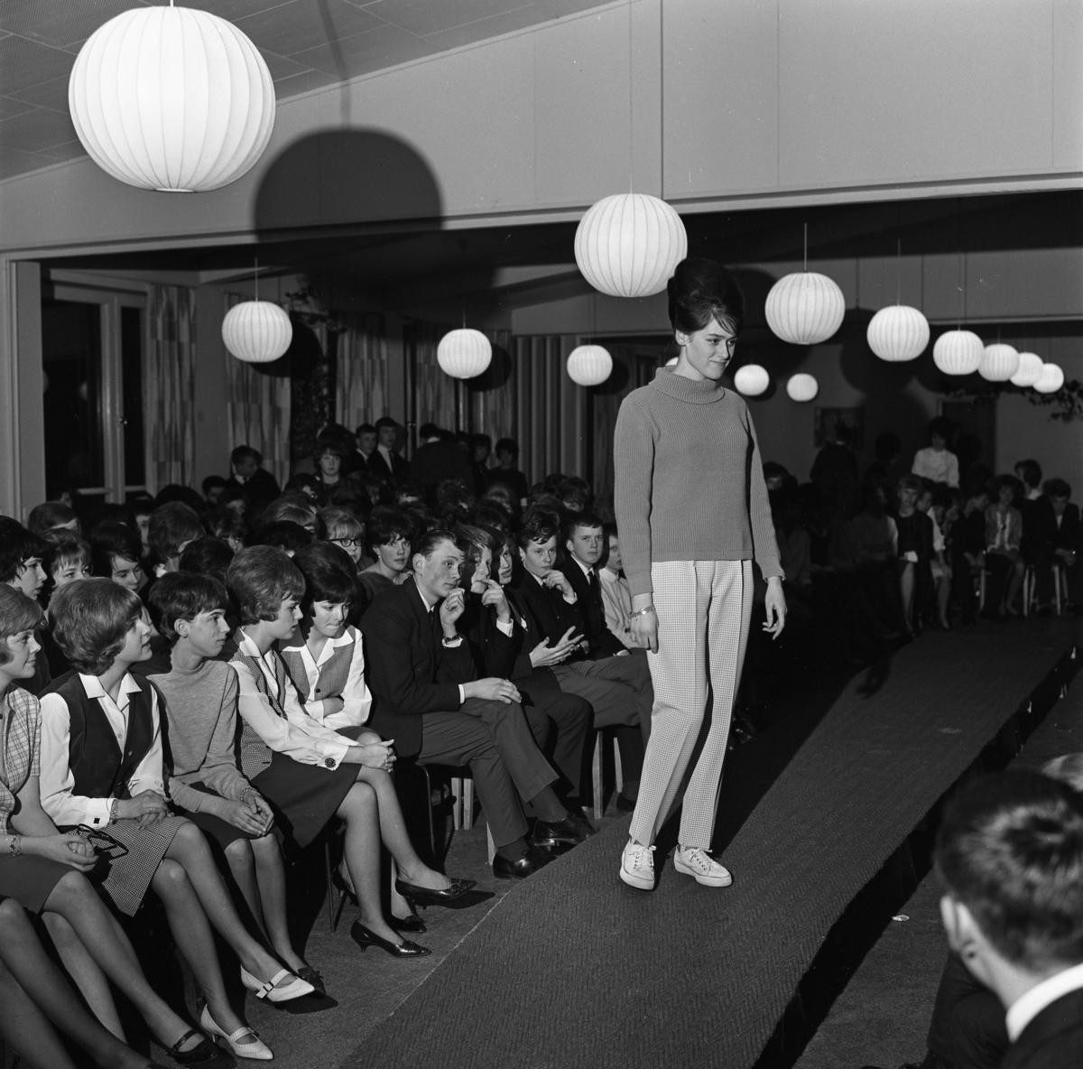 Ungdomsträff med modevisning. Ung kvinna visar polojumper och rutiga långbyxor. Publiken sitter i rader.