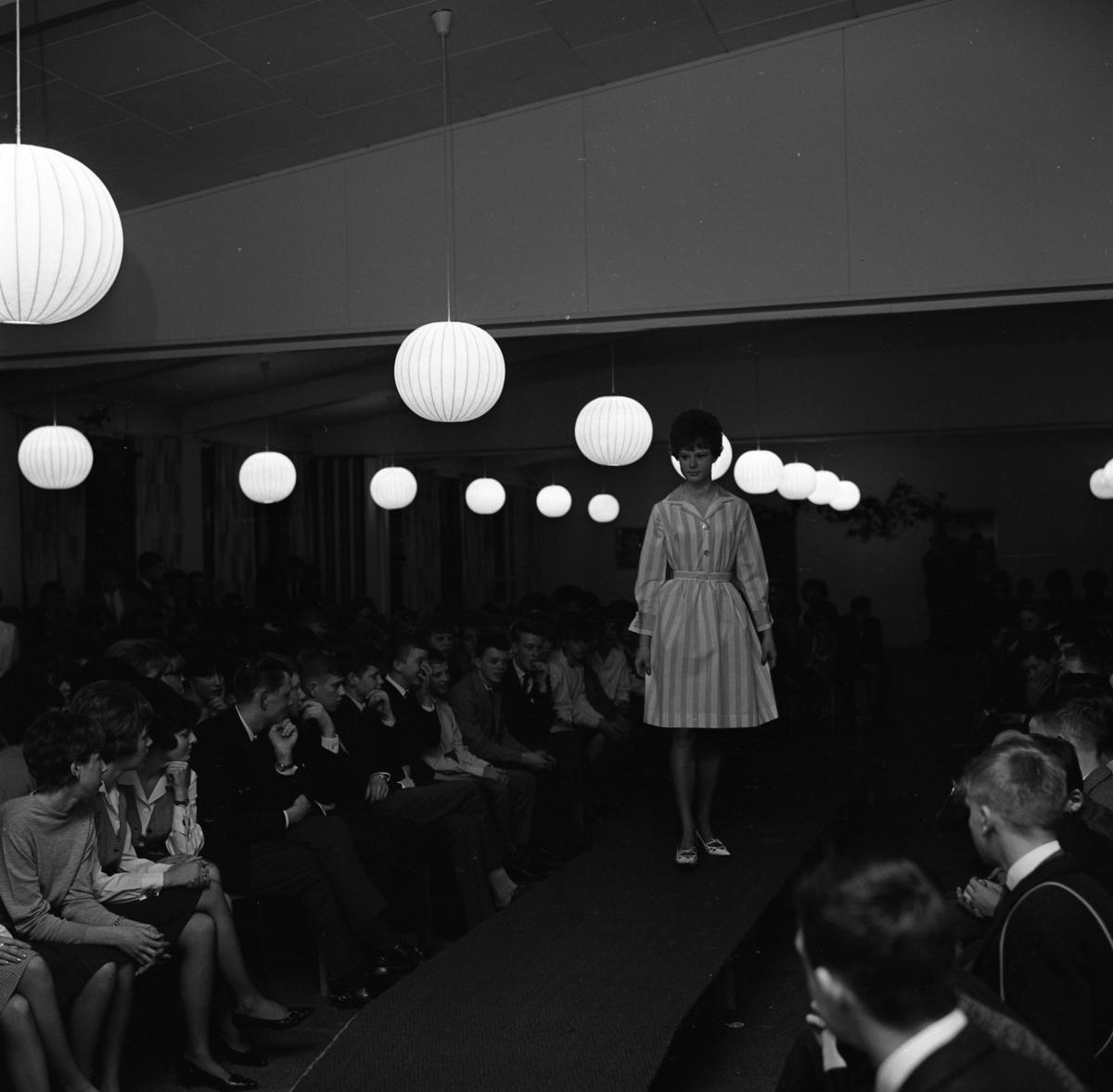 """Ungdomsträff med modevisning. Mannekängen bär långrandig klänning med krage, knytskärp och vidd i kjolen. Publiken sitter vid sidan av """"röda mattan""""."""