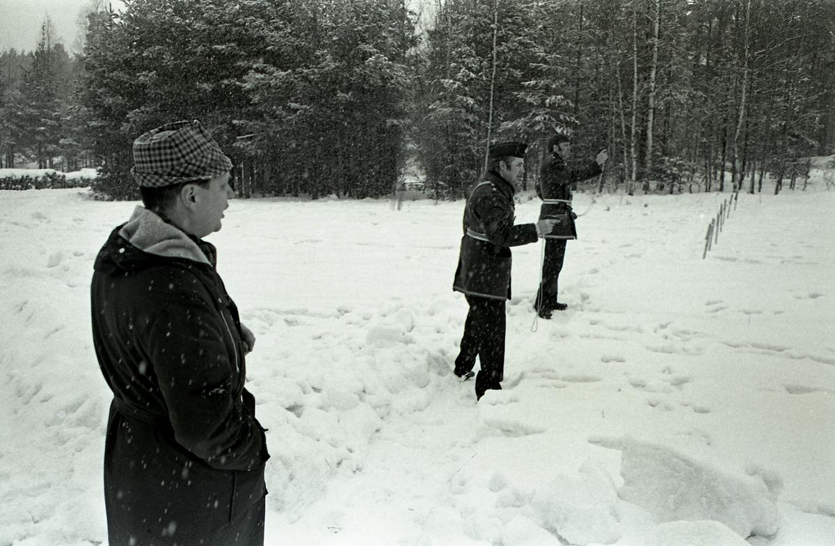 Polisen tränar pistolskytte. Två polismän, i uniform, skjuter med pistol. En man ser på. Det är vinter och snö.