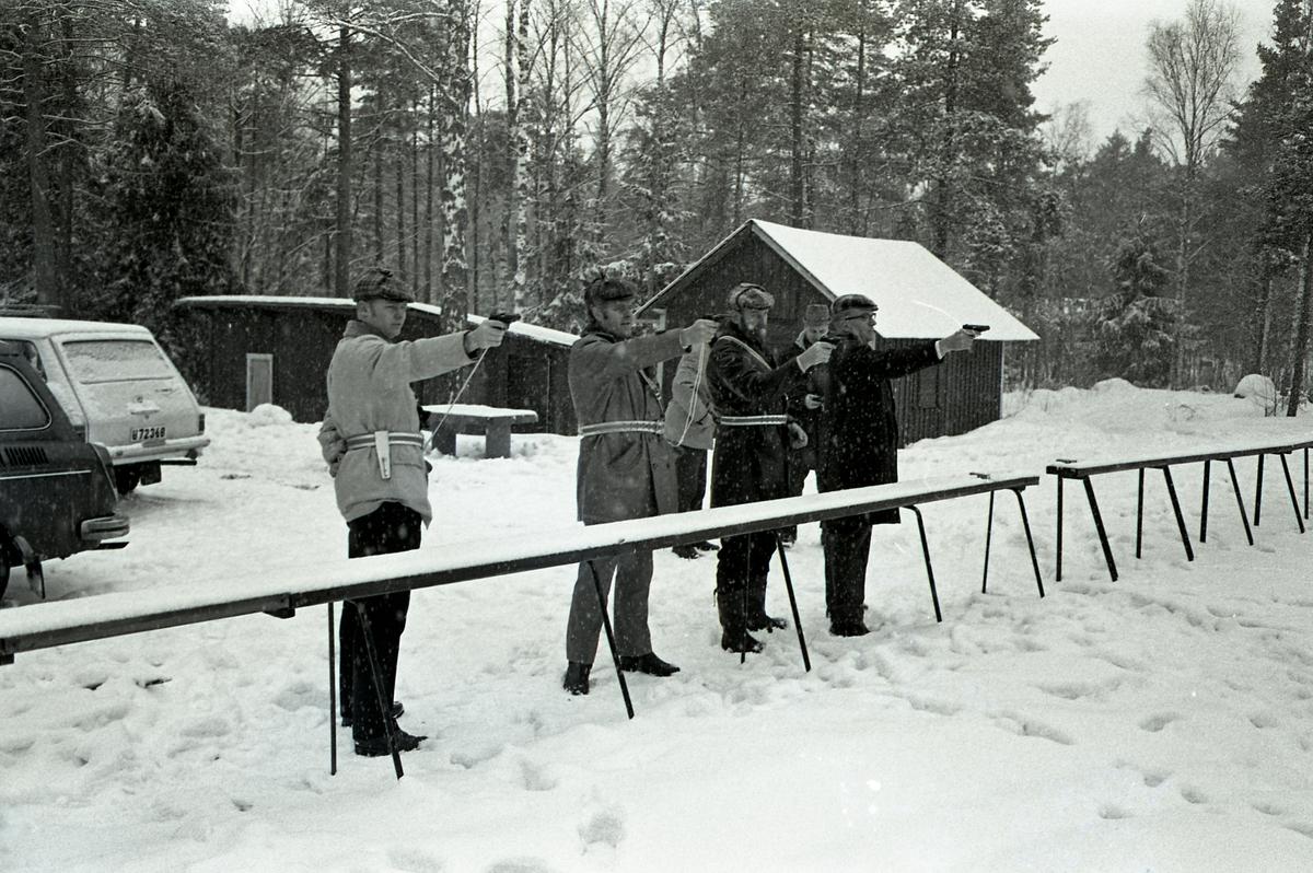 Polisen tränar pistolskytte. Fyra män uppställda. Det snöar. Ett litet hus och en bil i bakgrunden.