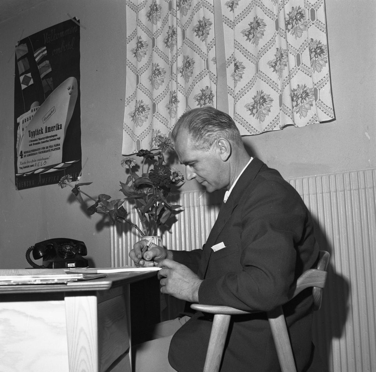 Resebyrån Reso i nya lokaler. En man sitter vid skrivbordet. Han har en penna i handen. En telefon och en vas med blommor står på skrivbordet. På väggen hänger en affisch som lockar med resor till Amerika.