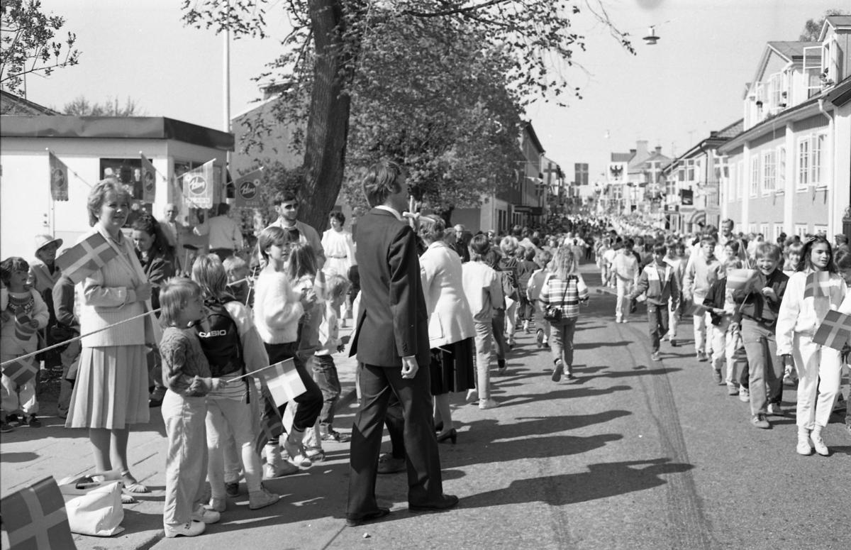 I Arboga firas minnet av Sveriges första riksdag. Det är 550-årsjubileum och staden gästas av kungaparet och högt uppsatta politiker. Skolbarn paraderar på Nygatan, österut. Många har flaggor i händerna. På trottoaren står människor och väntar. Till vänster ses en kiosk. Längre bort, på gatan, ligger bokhandeln och systembolaget (vänster sida). Riksdagsjubileet 1985