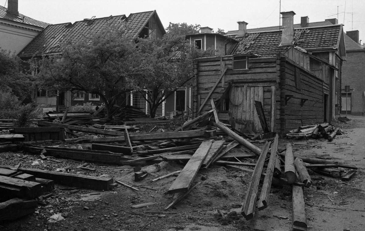 Rivning av en fastighet på Nygatan. Huset är en del av Glasbruksgården. Bräder och tjocka timmerstockar ligger på gården. Fruktträden står i bråten. Byggnaden ligger i hörnet Östra Nygatan - Vikingagatan.