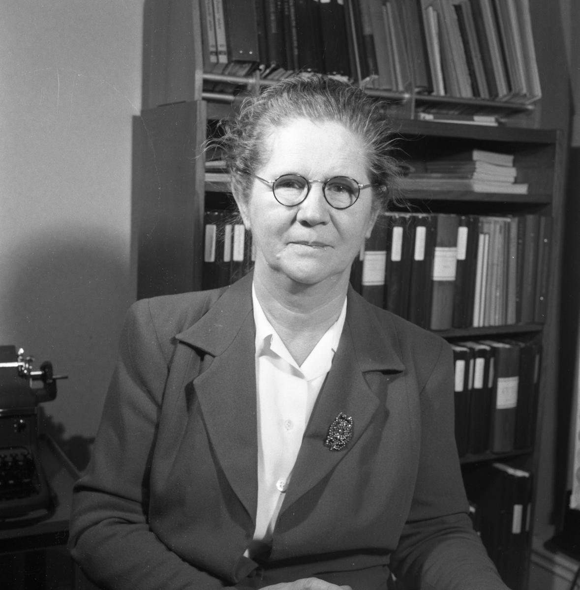 Telekommissarie Eva Geete/Eva Gethe på Televerket, Sohlénska huset, Nygatan. Eva bär glasögon och har en brosch på slaget på dräktjackan. Bakom henne skymtar en skrivmaskin och en bokhylla. Läs om Televerket och branden 1956 i Arboga Minnes årsbok 1993. Porträtt.