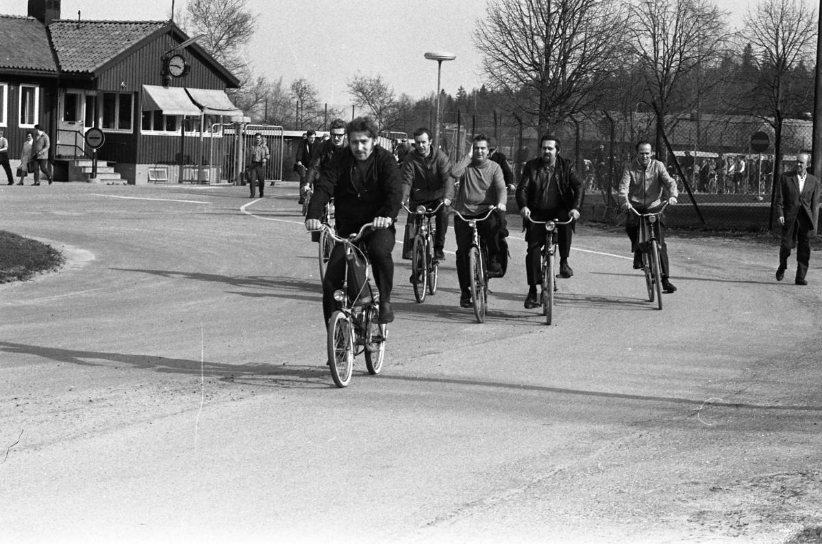 """Arbetsdagen är slut på CVA, Centrala Verkstaden Arboga. Ingenjörer och verkstadsarbetare är på väg hem på sina cyklar. I bakgrunden ses """"vakten"""" (byggnaden där vakten sitter) och grindarna."""