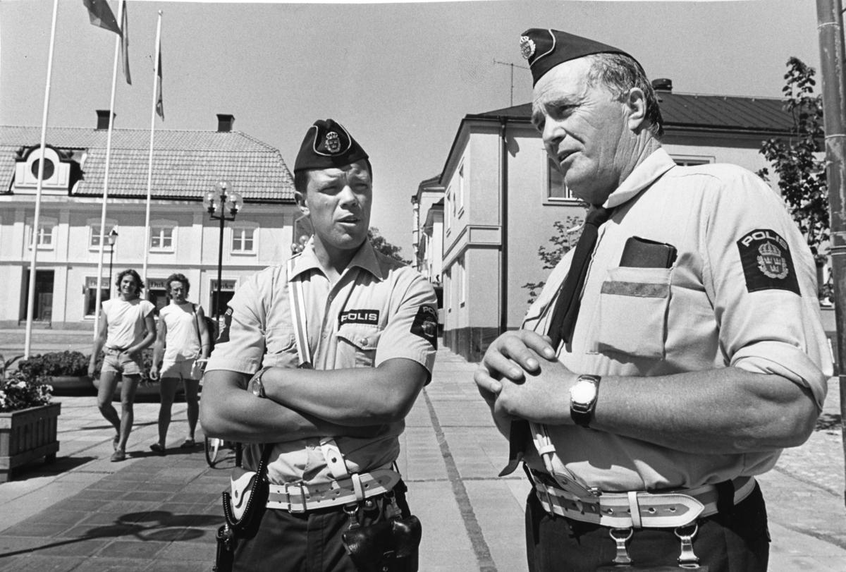 Två polismän på Stora torget. Två män i shorts ses i bakgrunden. I fastigheten till vänster har Yngvar Gunnarsson sin Duka-butik.  Blomsterplanteringar. Rådhuset till höger, utanför bild.