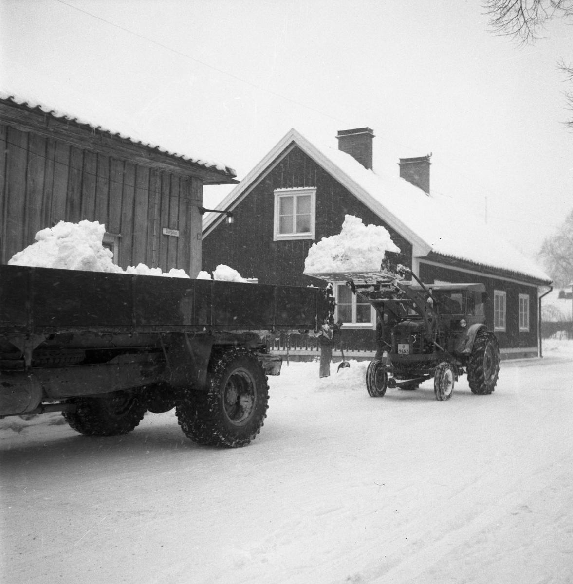 Snöröjning på Storgatan. En traktor med skopa lastar snö på en kärra.