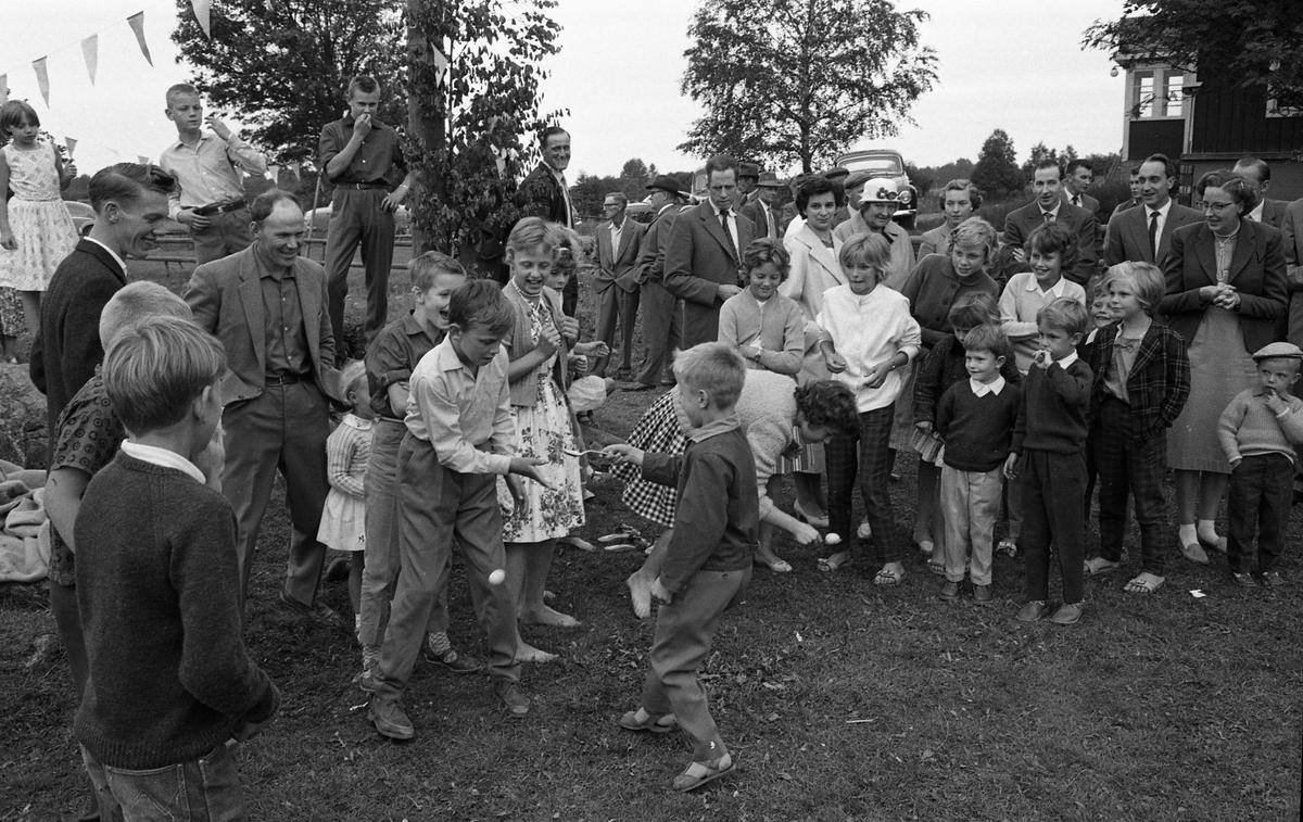 Festligheter i Algots hage i Tyringe. Här är det ägglöpning på gång. Stafettöverlämningen går inte så bra för Klas-Håkan Gustavsson (Findla) och Nils Arvidsson (Tyringe). Flickan som syns mellan pojkarna kommer från Sjölunda. Mannen i mörk kavaj, längst till vänster i bild, är Mats Pettersson (Lillebo). Bredvid honom står Henry Tyrfors (Tyringe). Strax till höger om mitten, i bilden, står Ulla Lindkvist i ljus kappa. Den unga kvinnan, till höger om Ulla, är Karin Lundgren (Skräddartorp). Mannen intill henne (som tittar på fotografen) heter Alvar. Bredvid honom står Beje. Kvinnan, längst till höger i bild, är Siv (Skräddartorp).